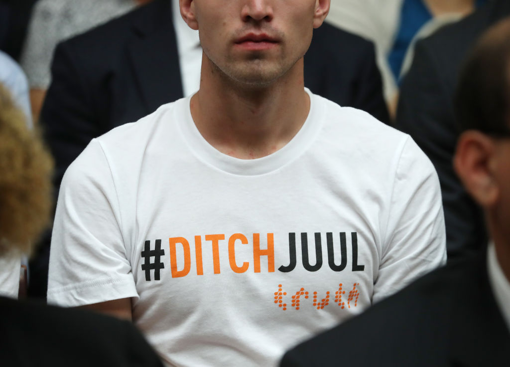 A young man wears a shirt that reads DITCHJUUL while James Monsees, co-founder of JUUL Labs, testifies before Congress in Washington, DC on July 25, 2019.
