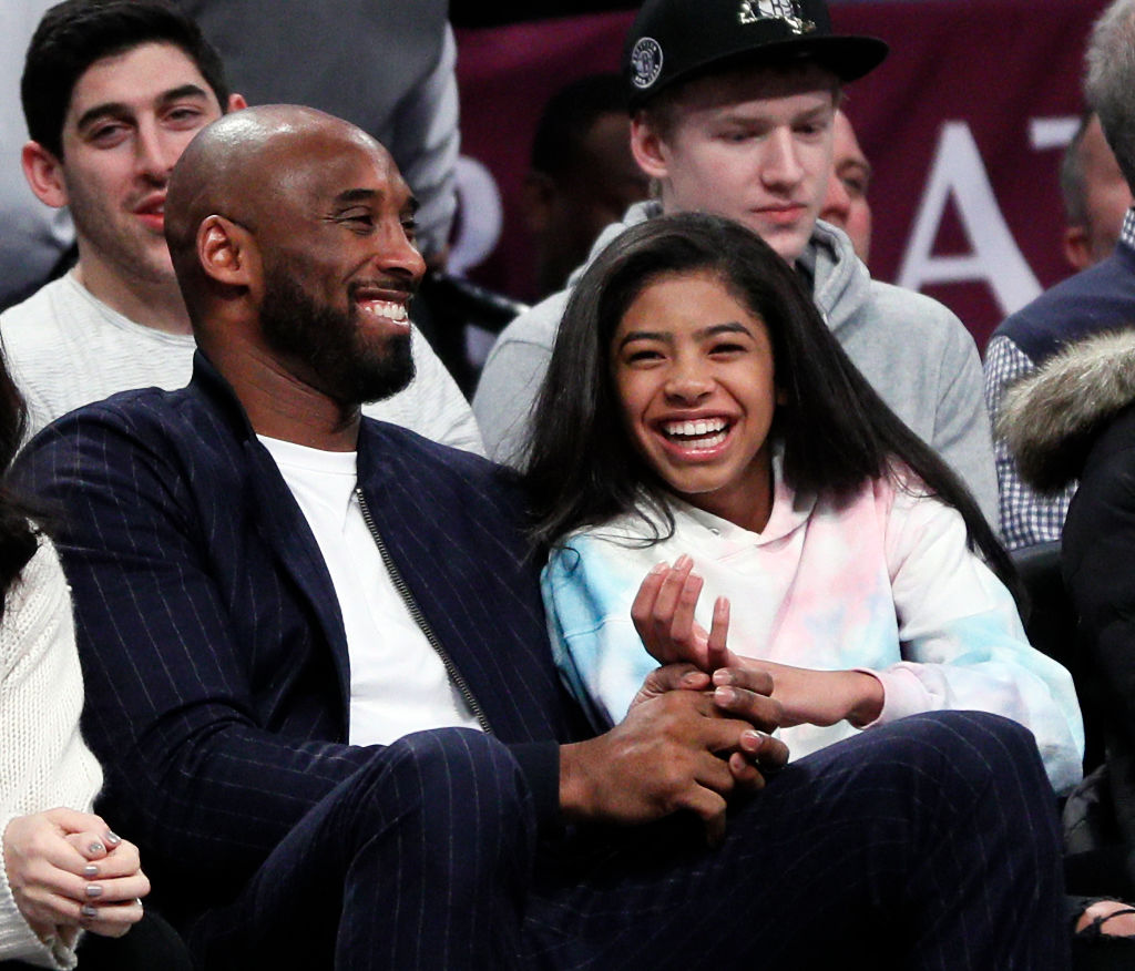 Retired NBA star Kobe Bryant and his daughter Gigi, watch an NBA basketball game between the Brooklyn Nets and Atlanta Hawks on December 21, 2019 at Barclays Center in the Brooklyn borough of New York City.
