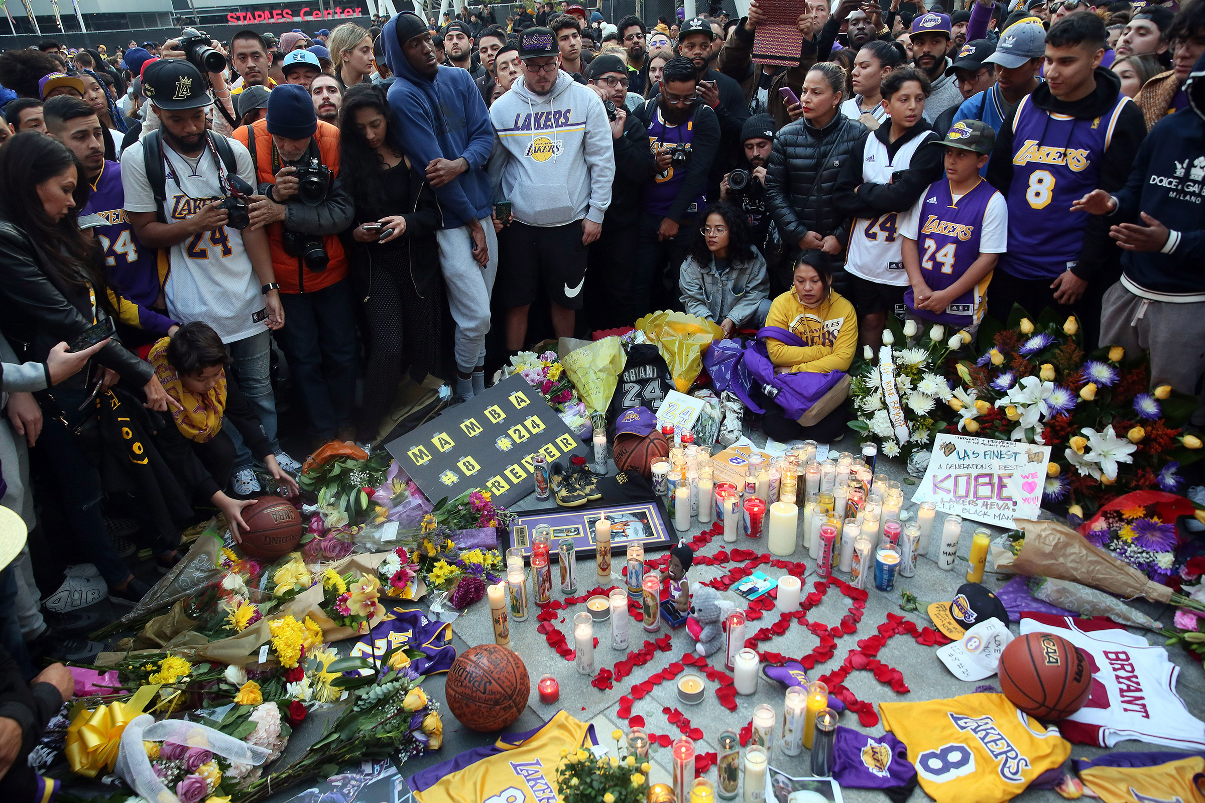 Fans place flowers, candles and memorabilia  during a vigil for late Los Angeles Lakers guard Kobe Bryant, at the LA Live entertainment complex across the street from the Staples Center in Los Angeles on Jan. 26, 2020.