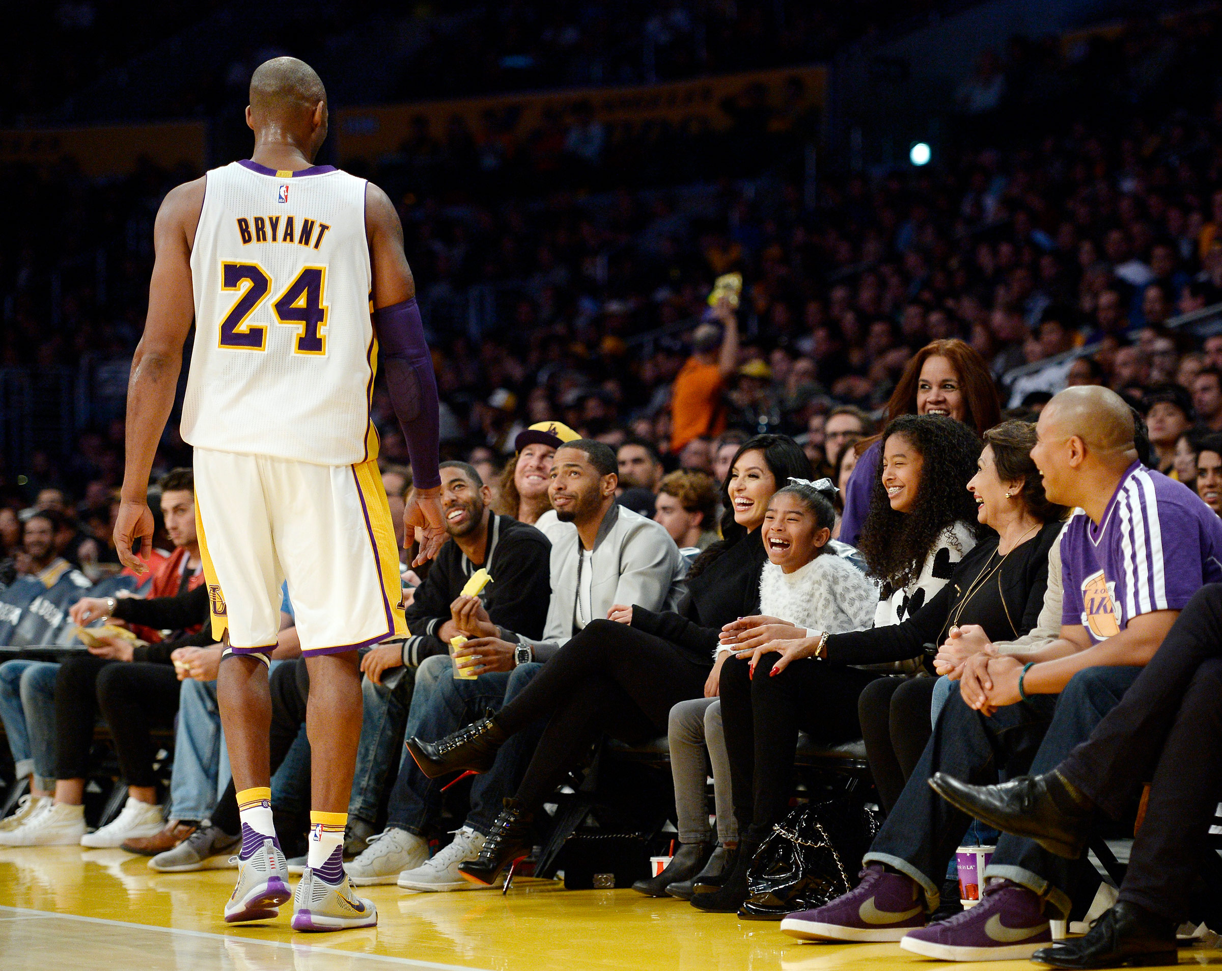 Kobe Bryant of the Los Angeles Lakers speaks with his daughters Gianna, 8, Natalia, 12, and wife Vanessa during the basketball game against the Indiana Pacersin Los Angeles, on Nov. 29, 2015