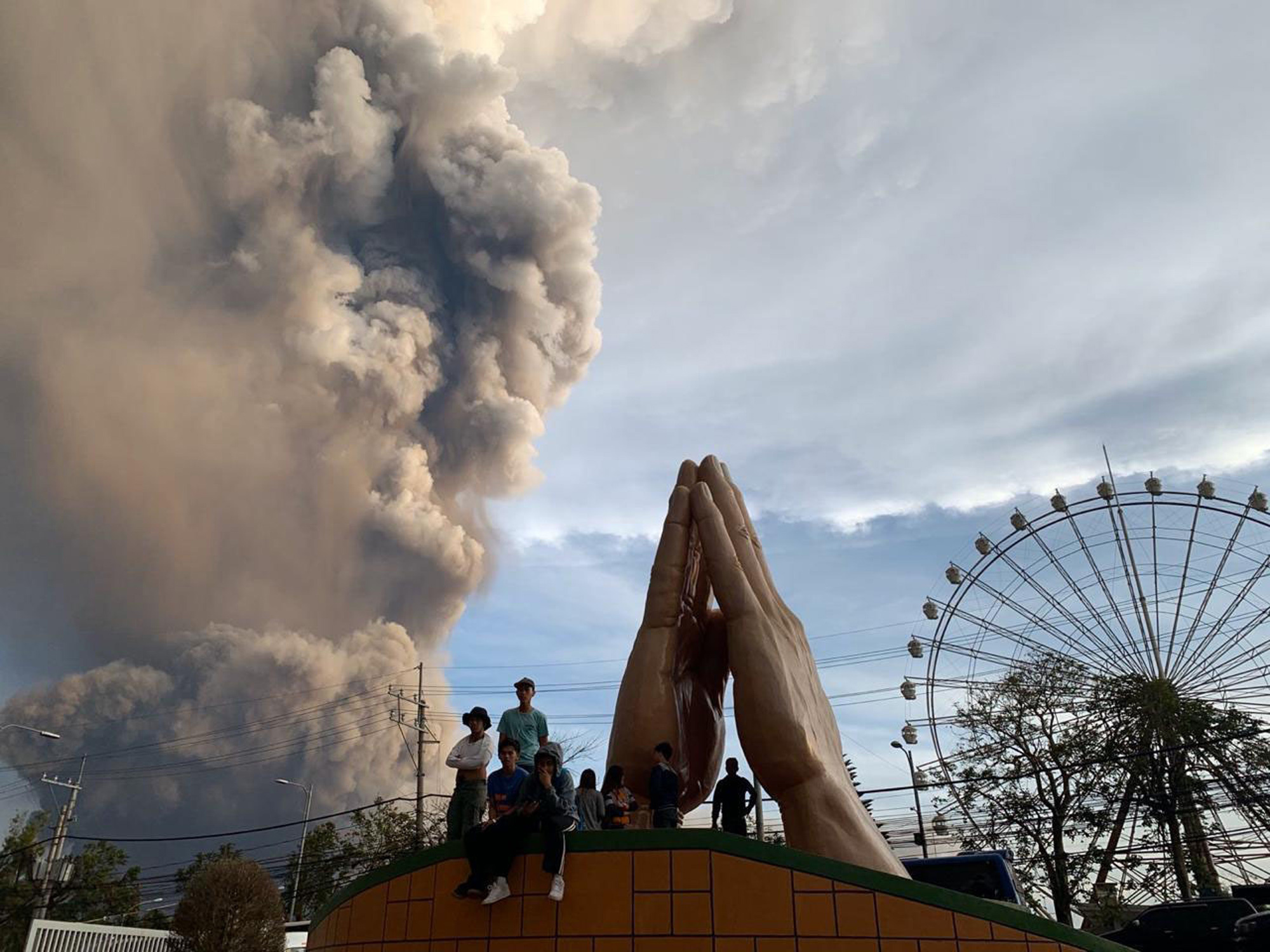 People watch as the Taal volcano spews ash and smoke during an eruption in Tagaytay, Cavite province south of Manila, Philippines on Jan. 12, 2020.
