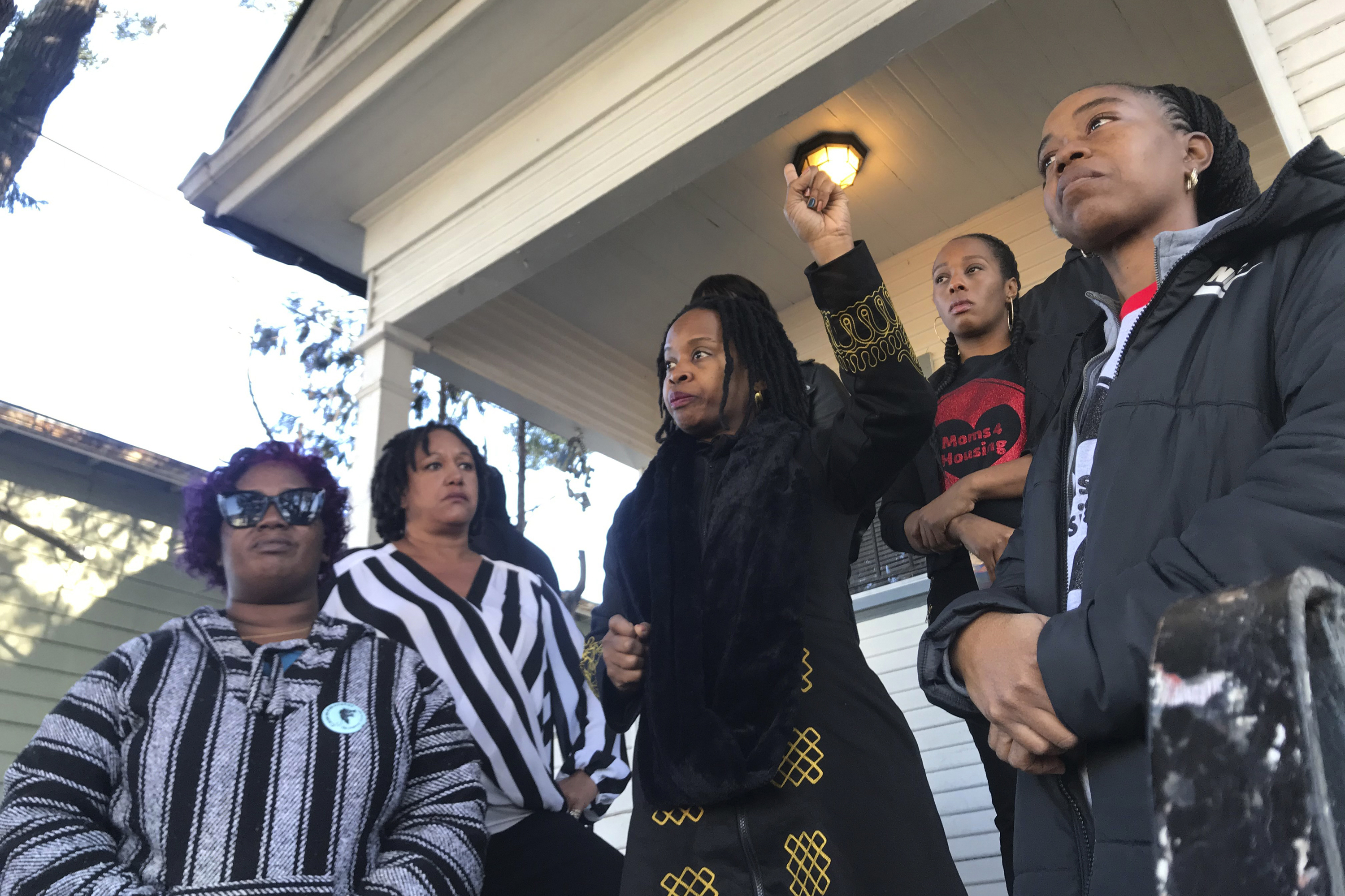 In this Dec. 30, 2019, file photo, Sharena Thomas, left, Carroll Fife, center, Dominique Walker, second from right, and Tolani KIng, right, stand outside a vacant home they took over on Magnolia Street in West Oakland, Calif.
