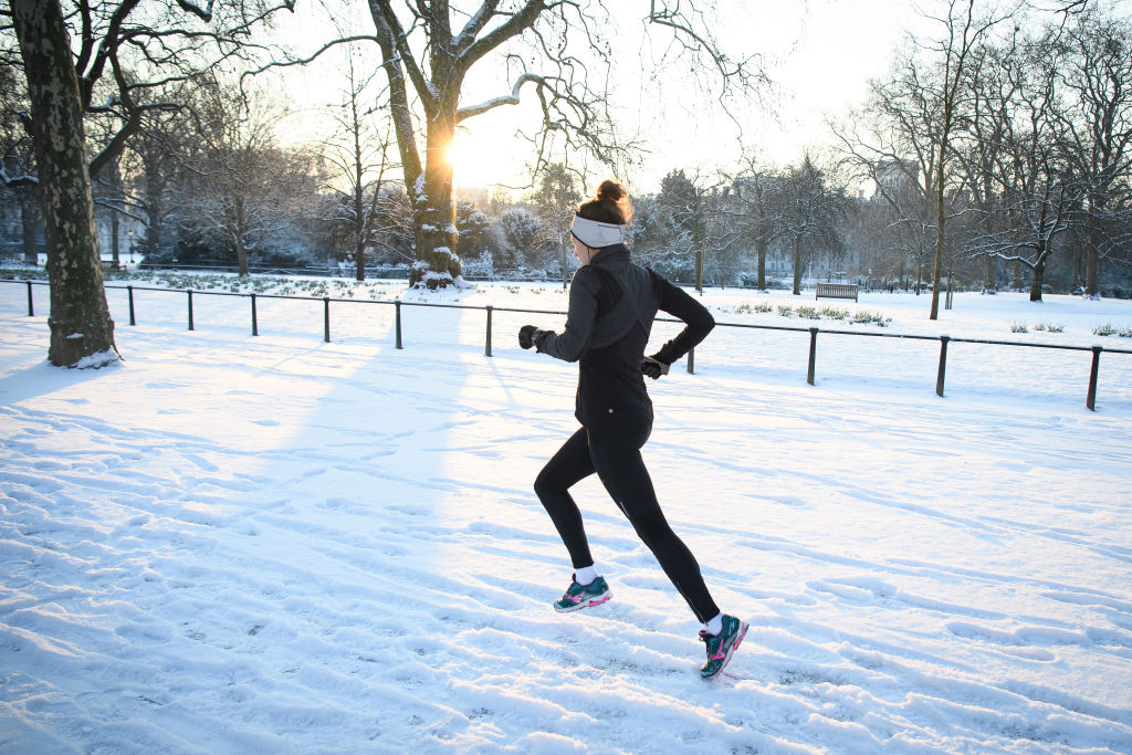 A jogger runs through the snow in St James' Park in London, on Feb. 28, 2018.
