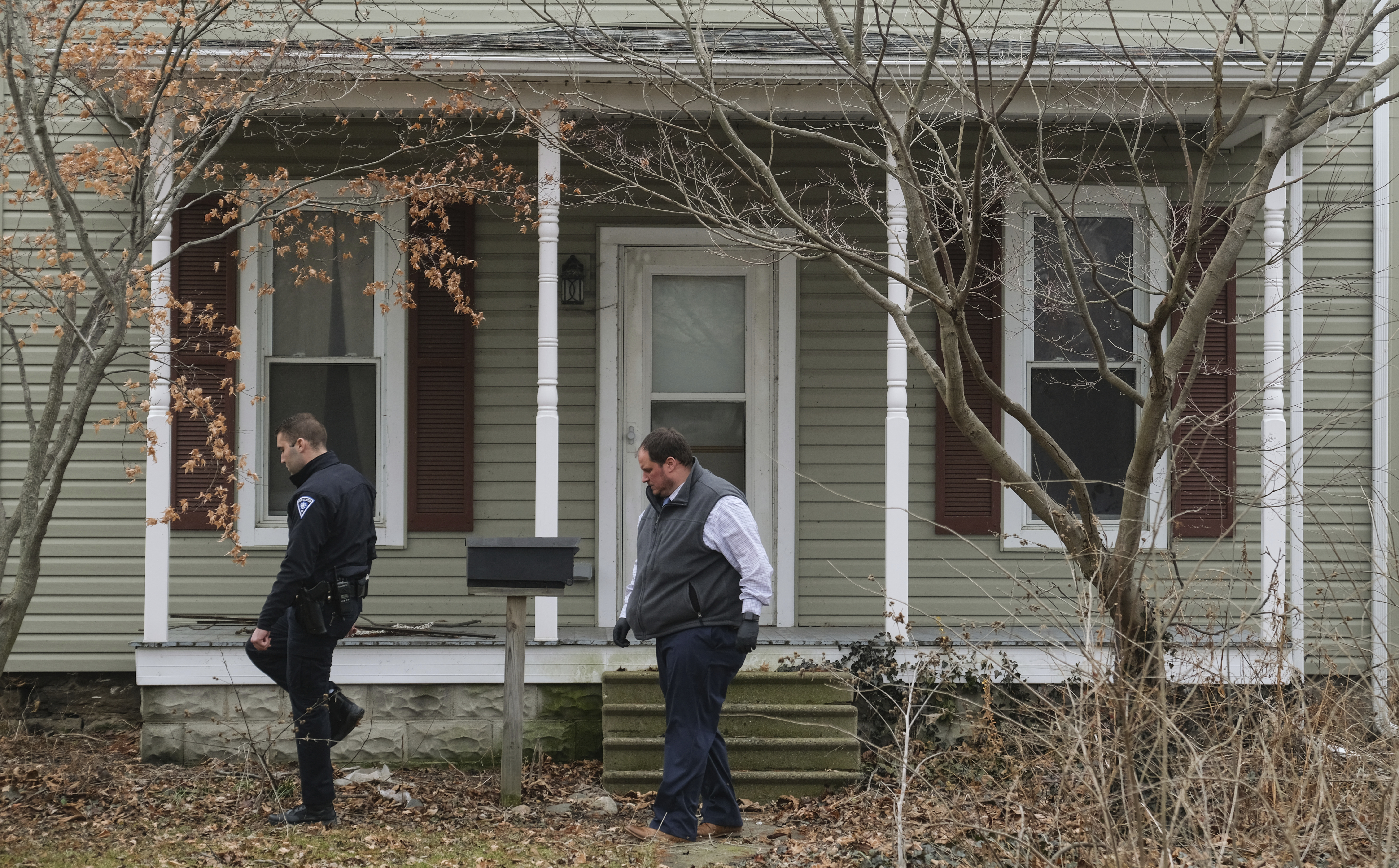 Law enforcement officers walk around a vacant house on Jan. 14, 2020, in Port Clinton, Ohio. where the body of Harley Dilly, 14, was found inside the chimney.