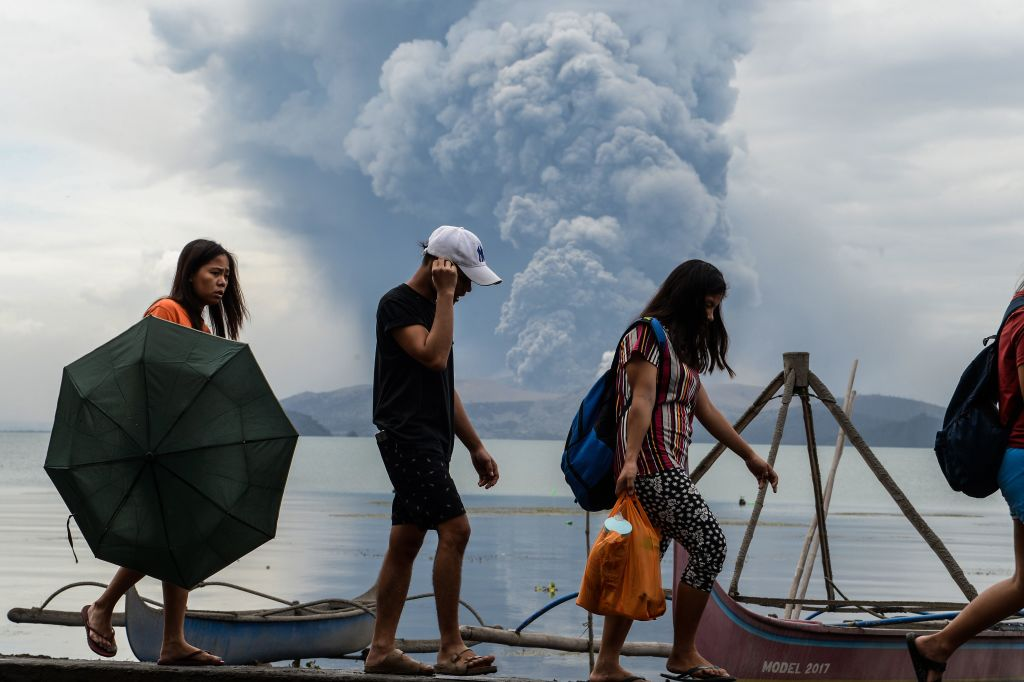 Residents walk past wooden boats as Taal volcano erupts, in Tanauan town, Batangas province south of Manila on January 13, 2020.