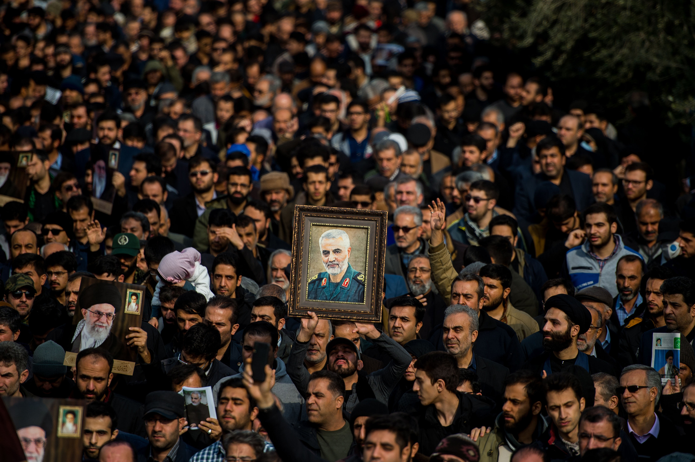 Protesters hold up a framed portrait of Qasem Soleimani, the Iranian commander killed in a U.S. drone strike in Baghdad, during a demonstration in Tehran, Iran, on Jan. 3, 2020.
