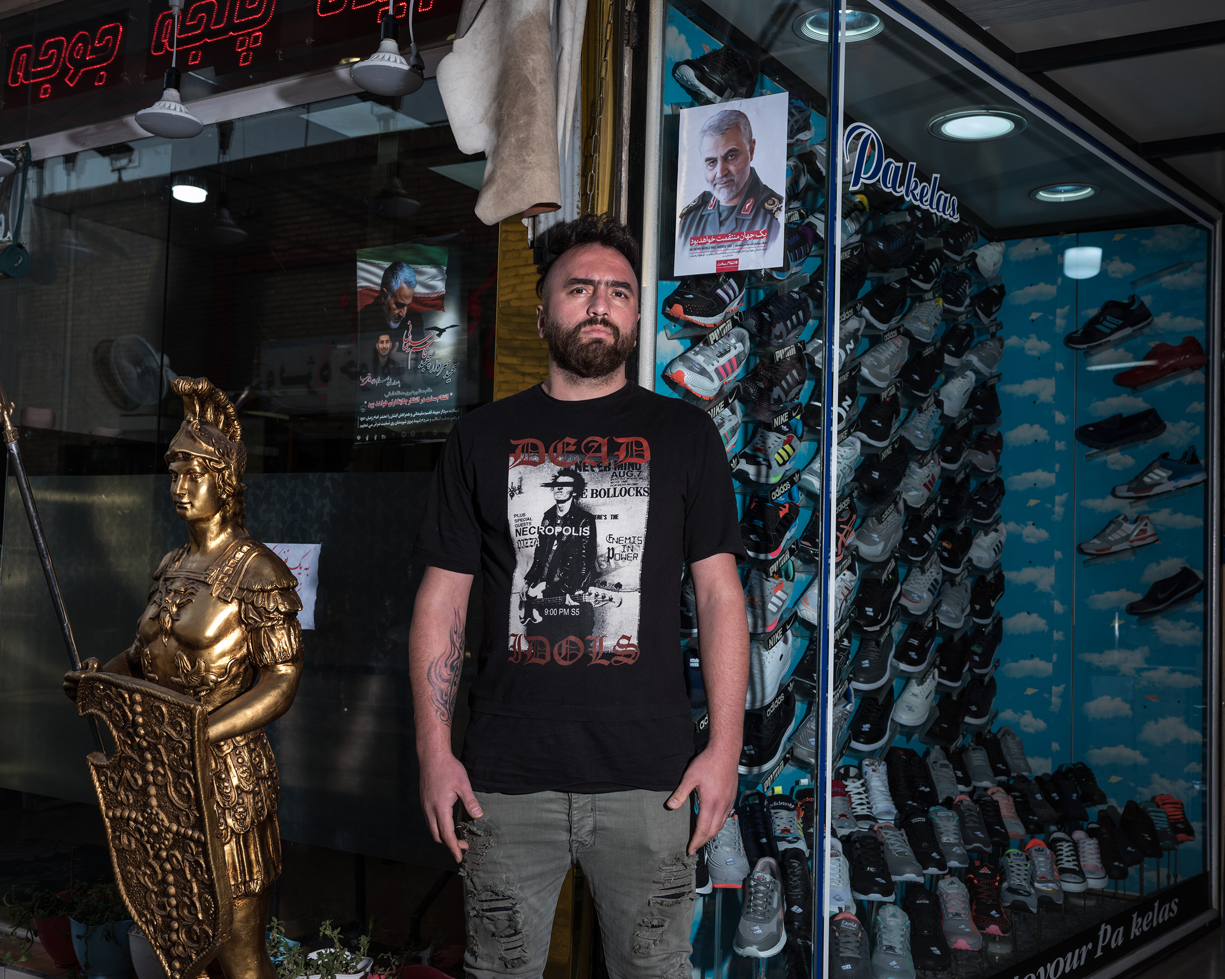 Ali, 29, sells shoes near the shrine to Shah Abdol Azim in Tehran. He hung a poster of Soleimani  out of respect for what he did for Iran.