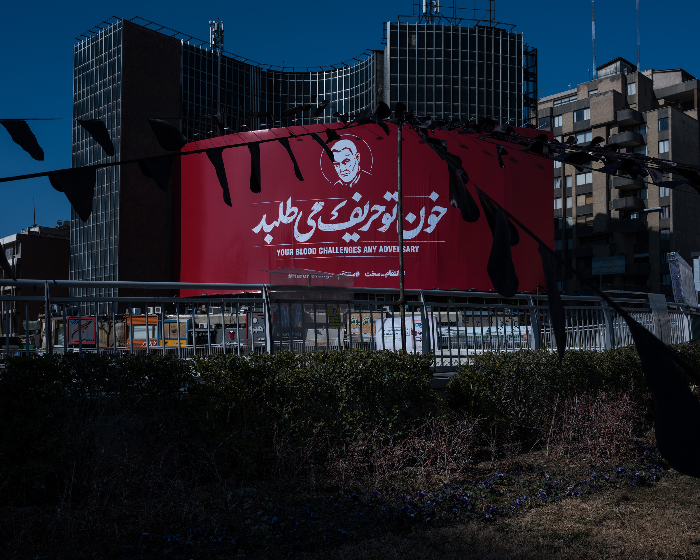 A massive banner showing Soleimani's likeness with the hashtag #HardRevenge hangs at Tehran's central Vali-e Asr Square.