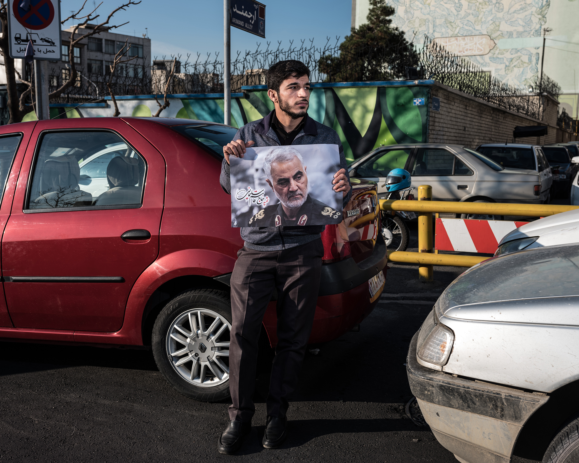A man holds a poster of Soleimani in traffic in Tehran.