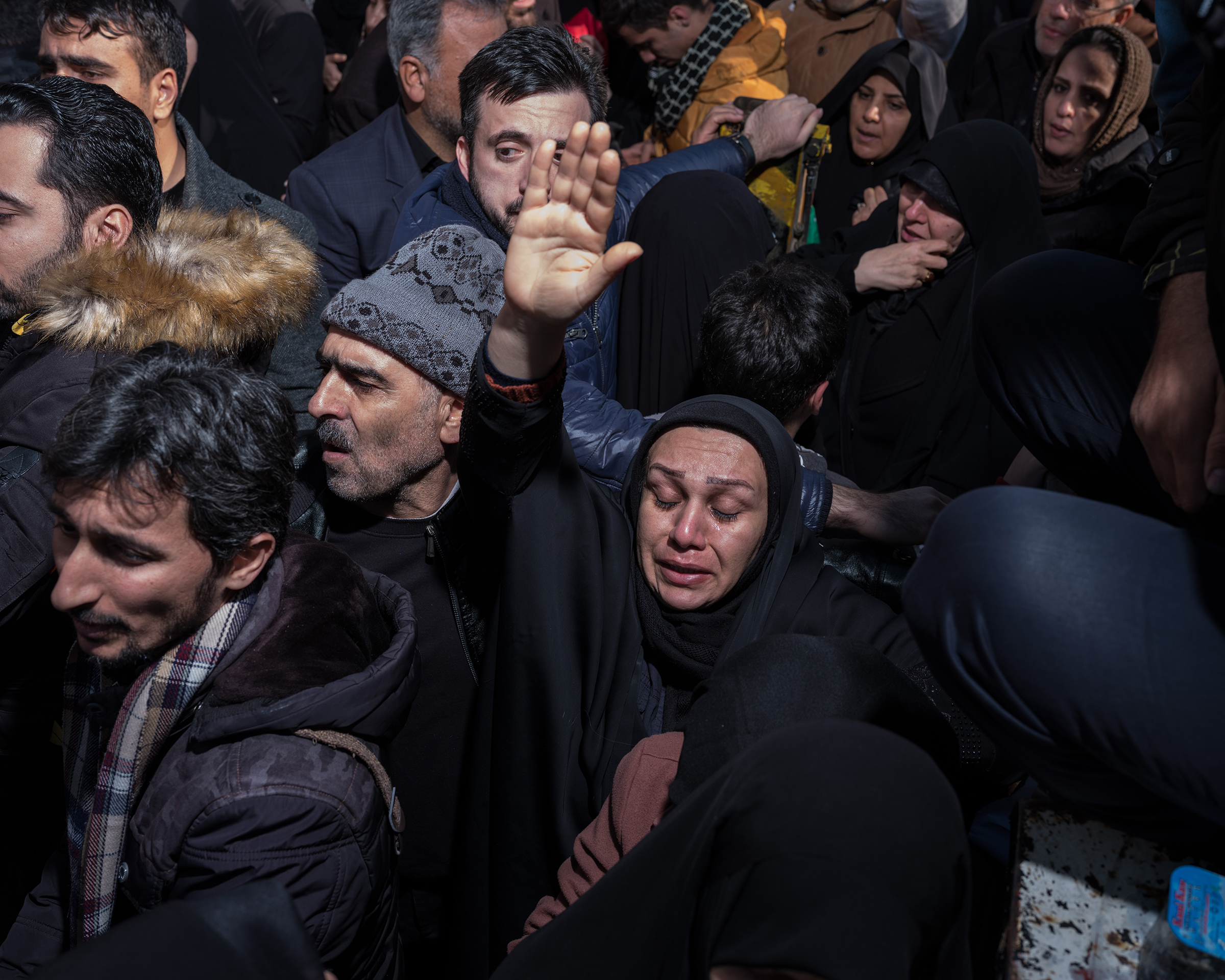 A woman raises her hand in a group of mourners.
