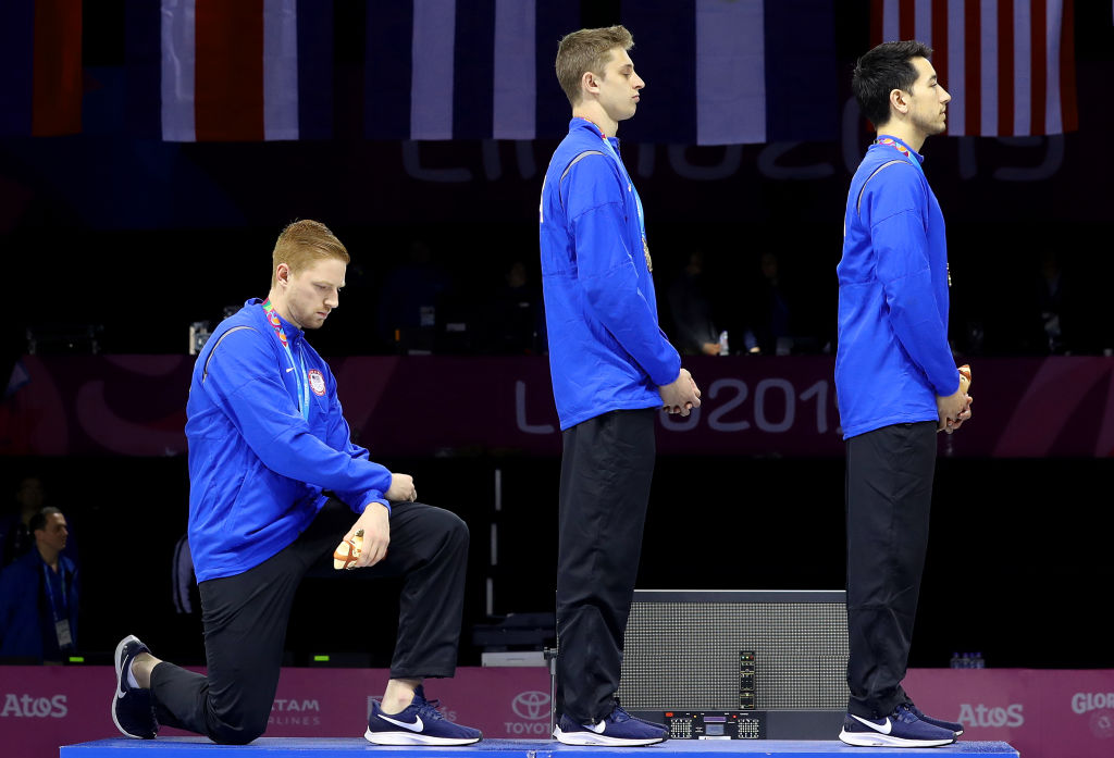 Gold medalist Race Imboden of the United States takes a knee during the National Anthem Ceremony on the podium of Fencing Men's Foil Team Gold Medal Match on Day 14 of Lima 2019 Pan American Games on August 09, 2019 in Lima, Peru.