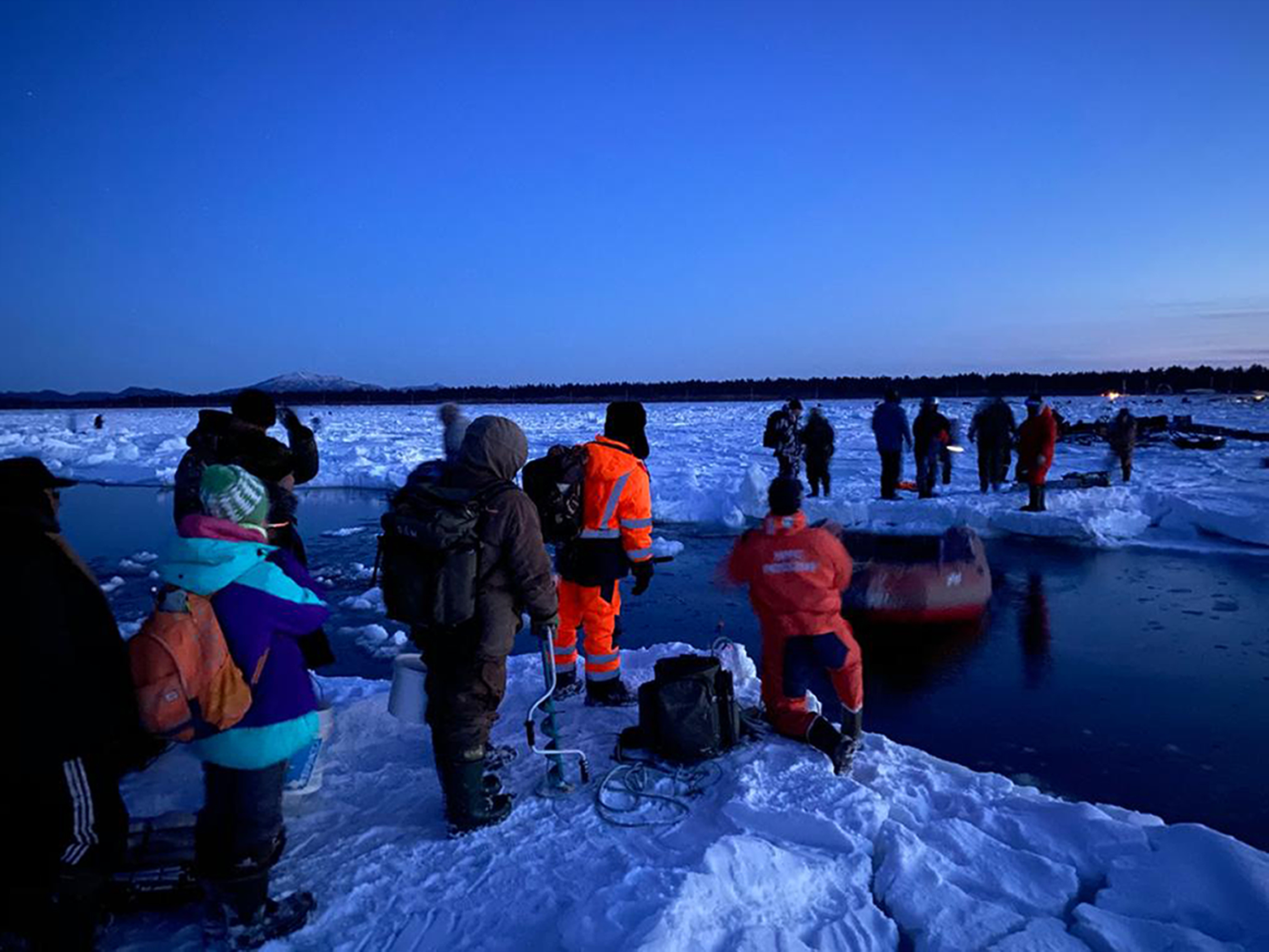 In this Jan. 28, 2020 photo released by the Russia Emergency Situations Ministry press service, rescuers help a group of fishermen get to land, using a small boat at Mordvinov's Bay in eastern Siberia, Russia.