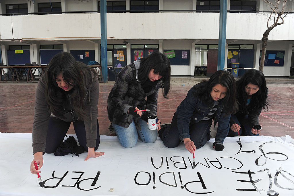 Students from the A-7 public high school for girls paint a banner during a peaceful occupation of the teaching institute in Santiago, on August 14, 2012, during a period of mass student protests.
