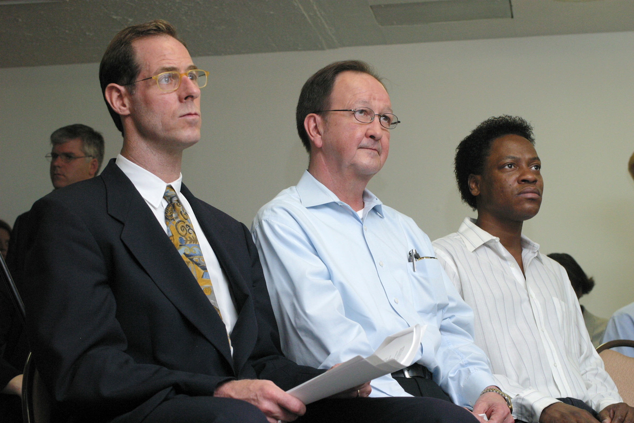 The two men who spent the night in jail in 1998 on sodomy charges, John Lawrence, center, and Tyron Garner, right, sit with their attorney Lee Taft, left, during a press conference in Houston on June 26, 2003.