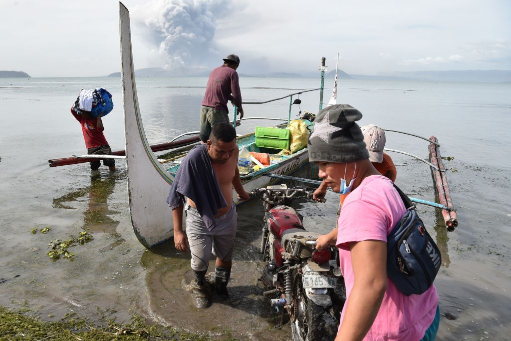 Evacuating residents unload their belongings from an outrigger canoe while the Taal volcano spews ash as seen from Tanauan town south of Manila on Jan. 13, 2020.