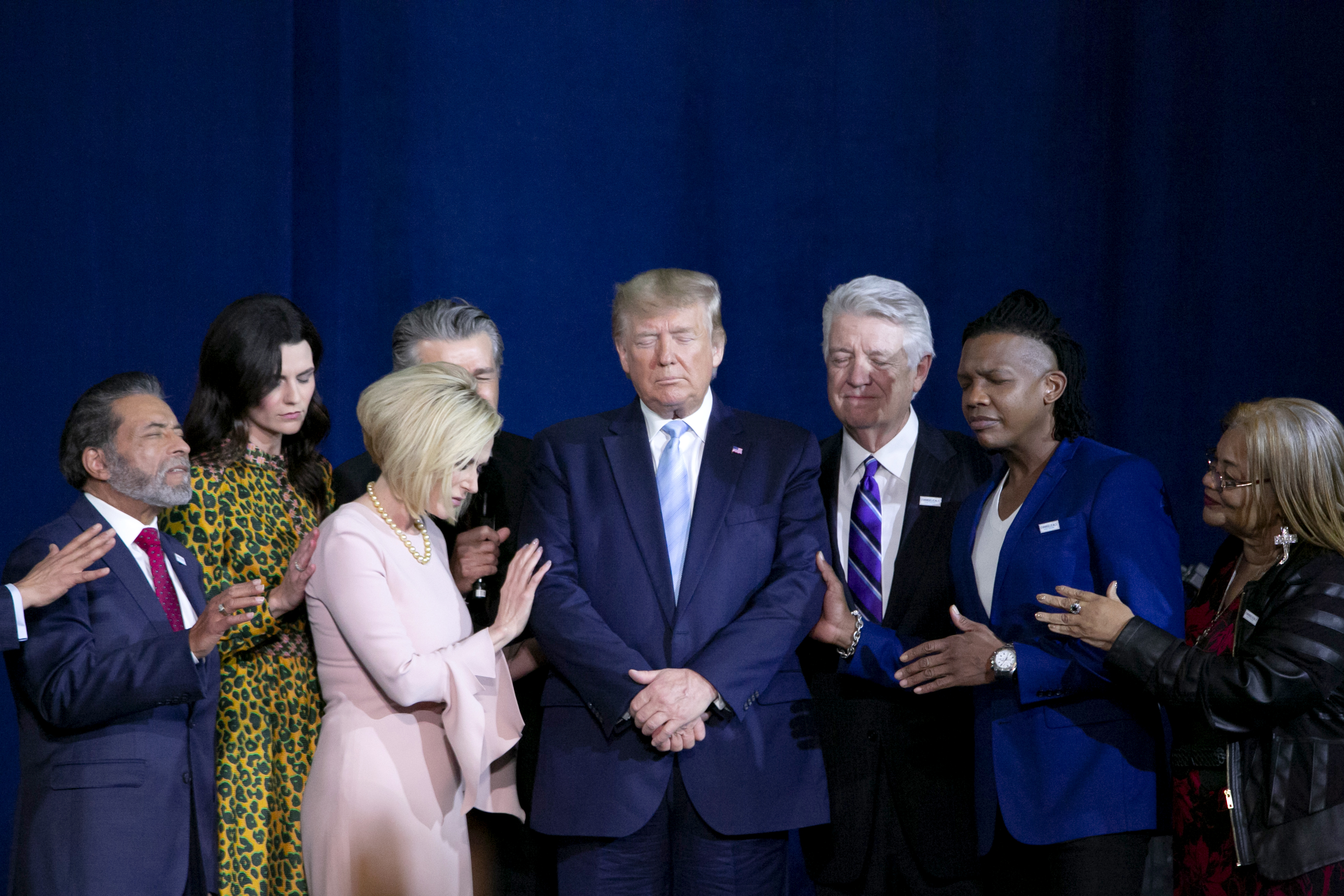 President Donald Trump, center, prays during an 'Evangelicals for Trump' Coalition launch event in Miami, Florida, on Jan. 3, 2020.