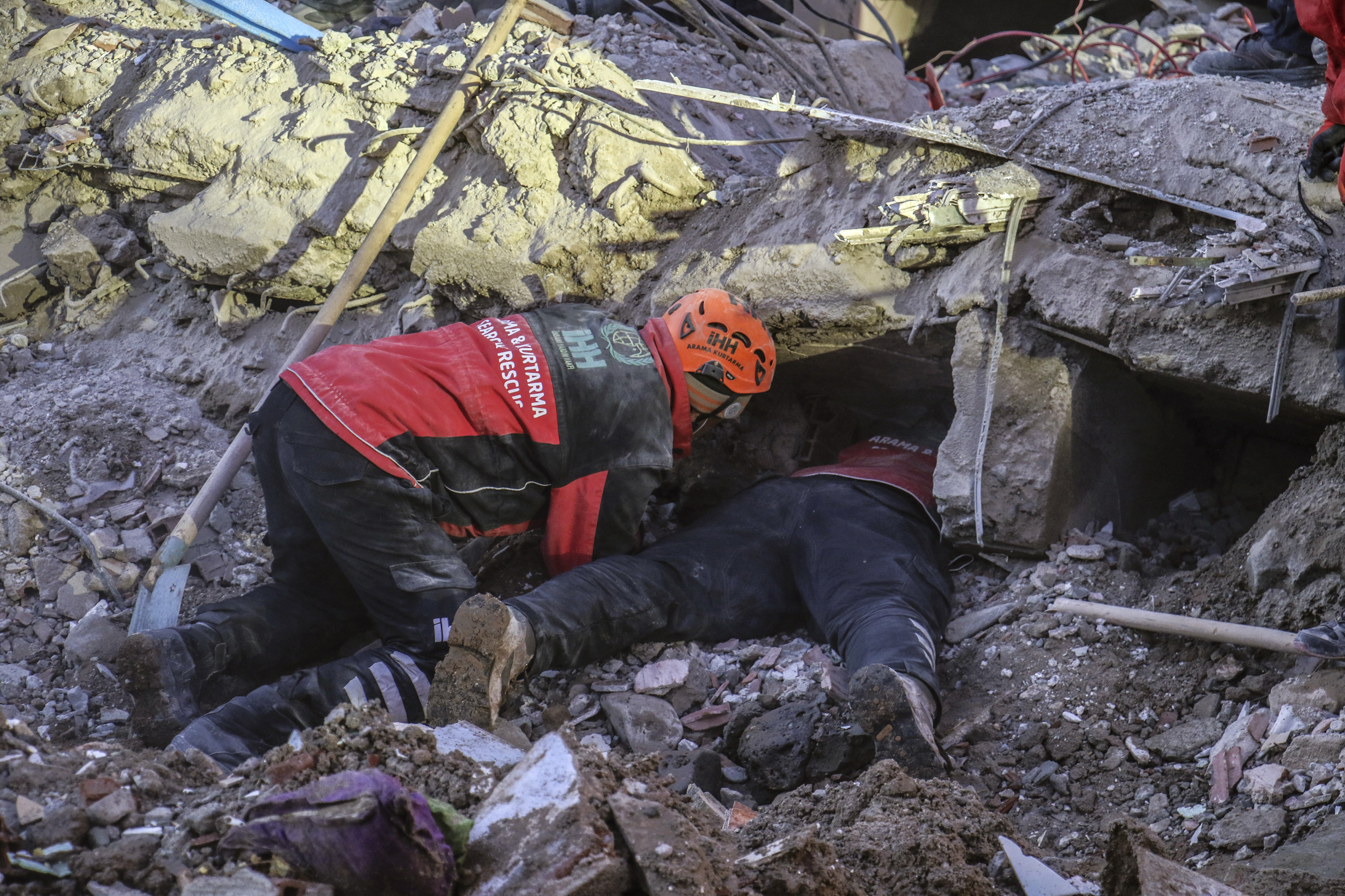 Rescue workers try to save people trapped under debris following a strong earthquake that destroyed several buildings on Friday, in Elazig, eastern Turkey, on Jan. 26, 2020.