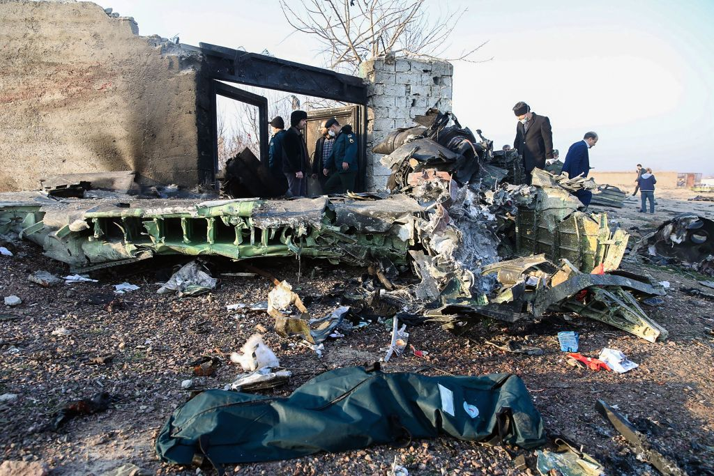 People stand near the wreckage after a Ukrainian plane carrying 176 passengers crashed near Imam Khomeini airport in Tehran on Jan. 8, 2020.