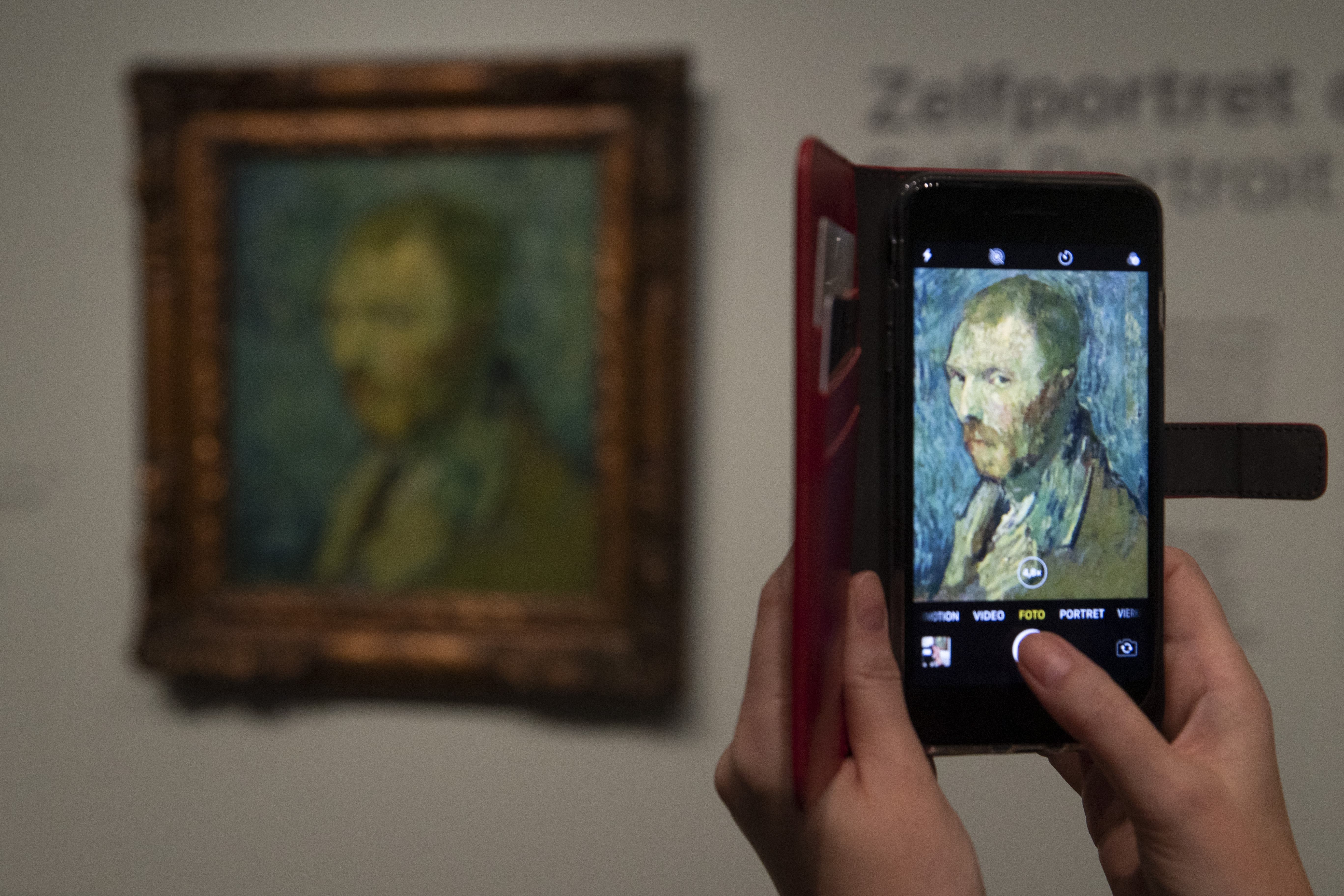 A journalist takes a picture of the previously contested painting by Dutch master Vincent van Gogh, a 1889 self-portrait, during a press conference in Amsterdam, Netherlands, on Jan. 20, 2020.