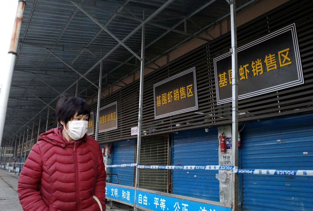 A woman walks in front of the closed Huanan wholesale seafood market, where health authorities say a man who died from a respiratory illness had purchased goods from, in the city of Wuhan, Hubei province, on Jan. 12, 2020.