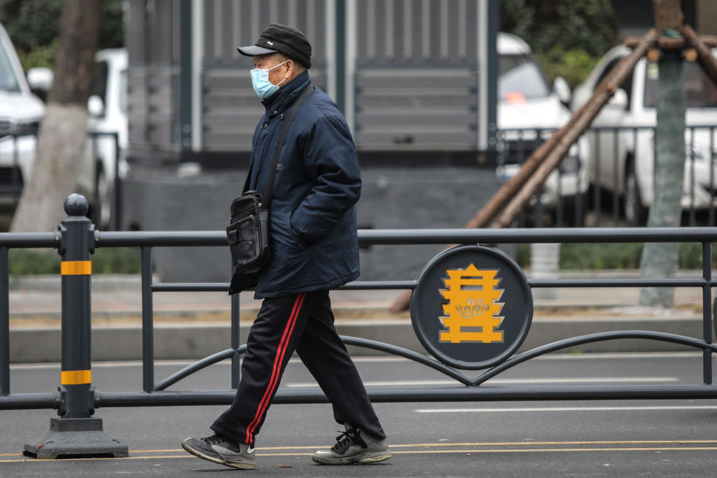 An elderly man wears a mask while walking past the closed Huanan Seafood Wholesale Market, which has been linked to cases of coronavirus, in Wuhan, China on Jan. 17, 2020.