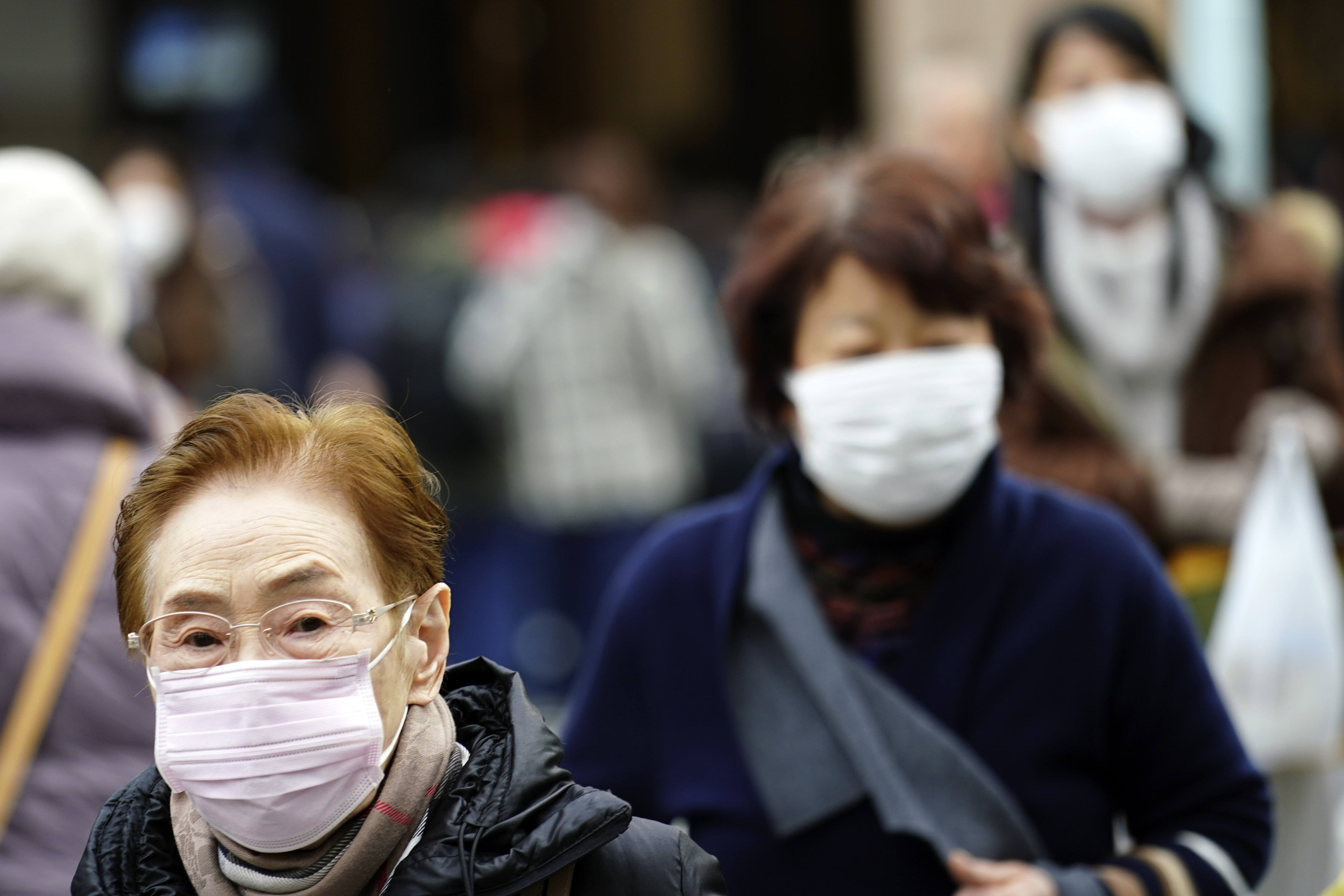 Pedestrians wear protective masks as they walk through a shopping district in Tokyo, Japan, on Jan. 16, 2020.
