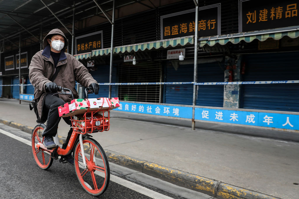 A man wears a mask while riding a bike past the closed Huanan Seafood Wholesale Market, which has been linked to the coronavirus in Wuhan, Hubei province, China on Jan. 17, 2020.