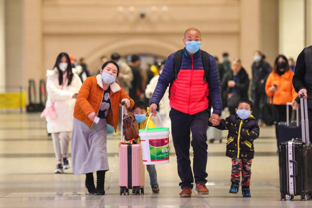 Passengers wearing protective masks walk inside Hankou Railway Station in Wuhan, China, on Jan. 21, 2020.