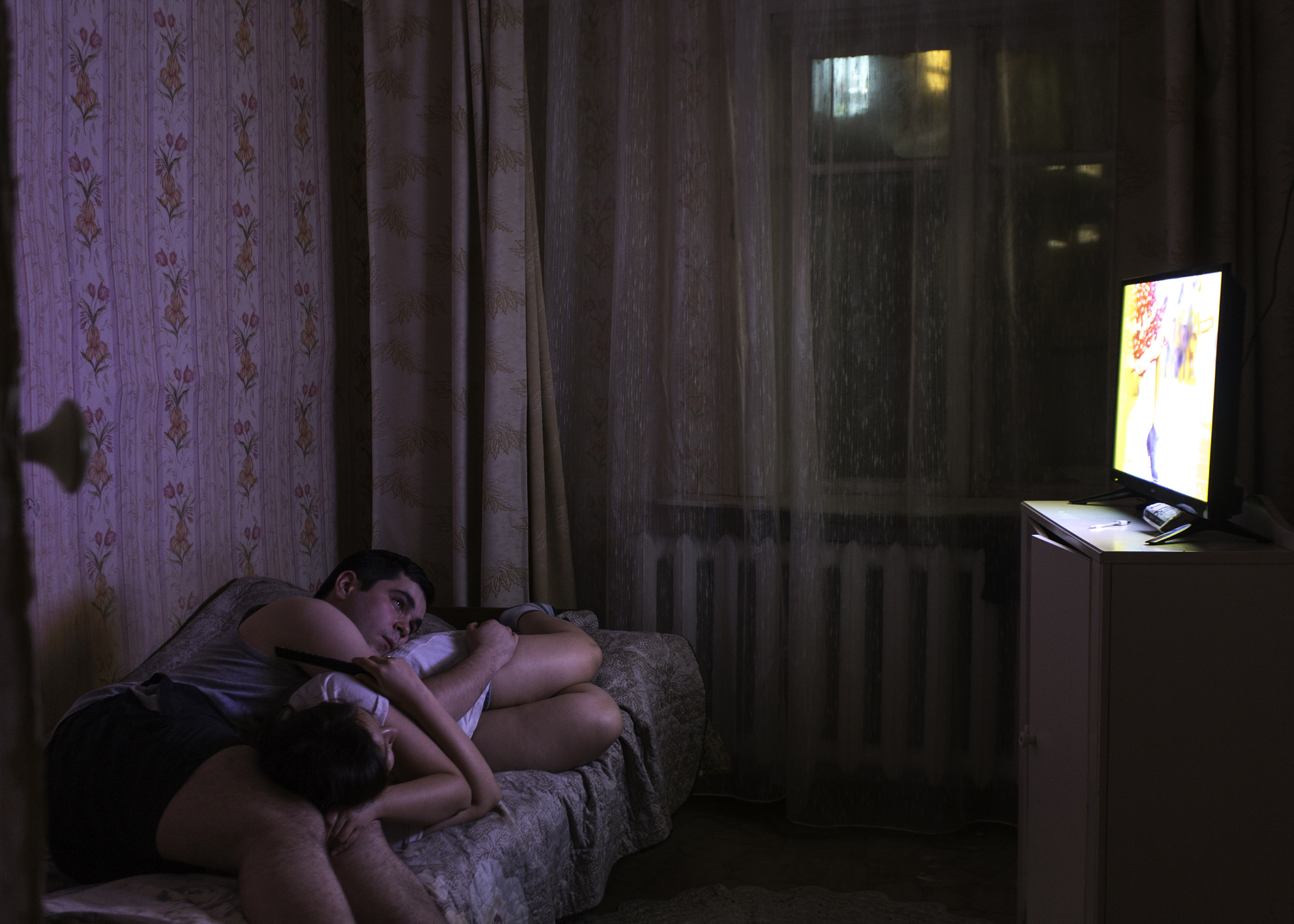 A young couple Ivan and Inna watch TV at home in Yakutia. There are several Yakut TV channels with 24/7 broadcasting.