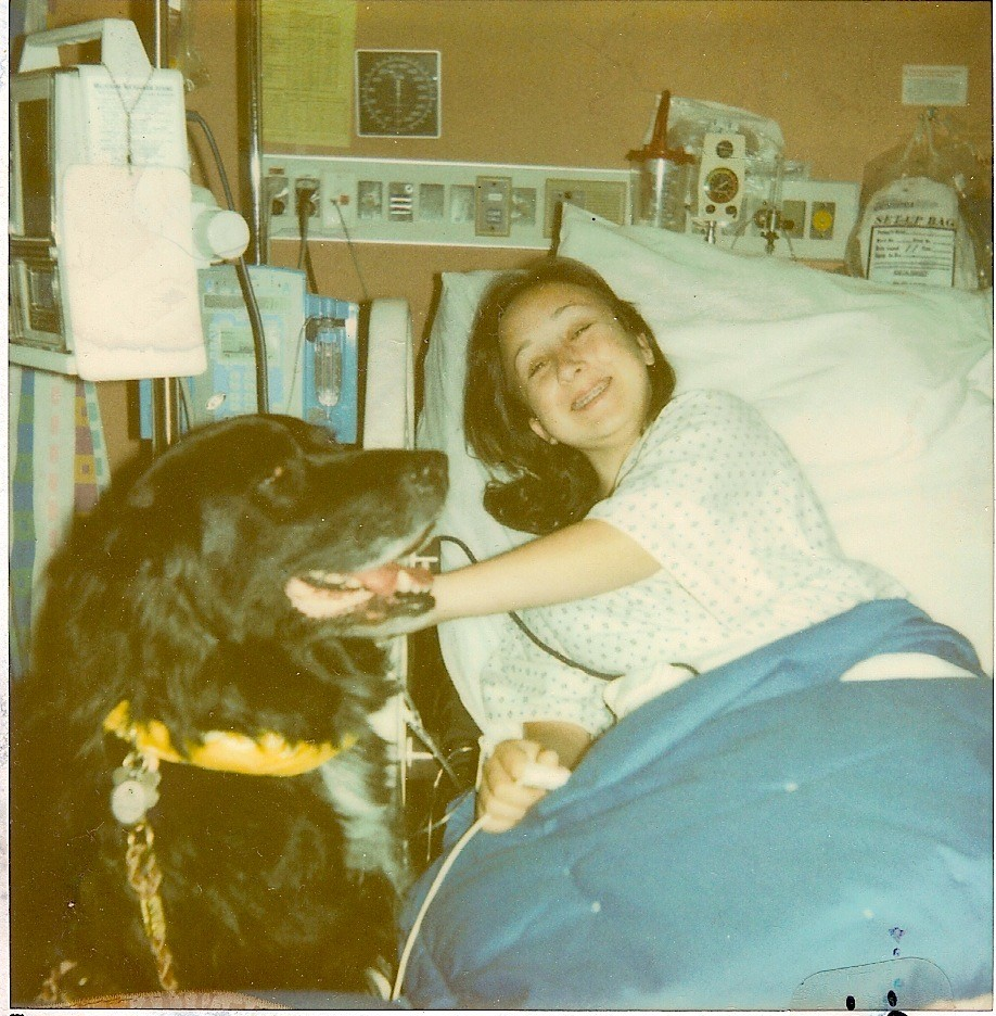 The author, at 14 years old, visited in the hospital by a therapy dog.