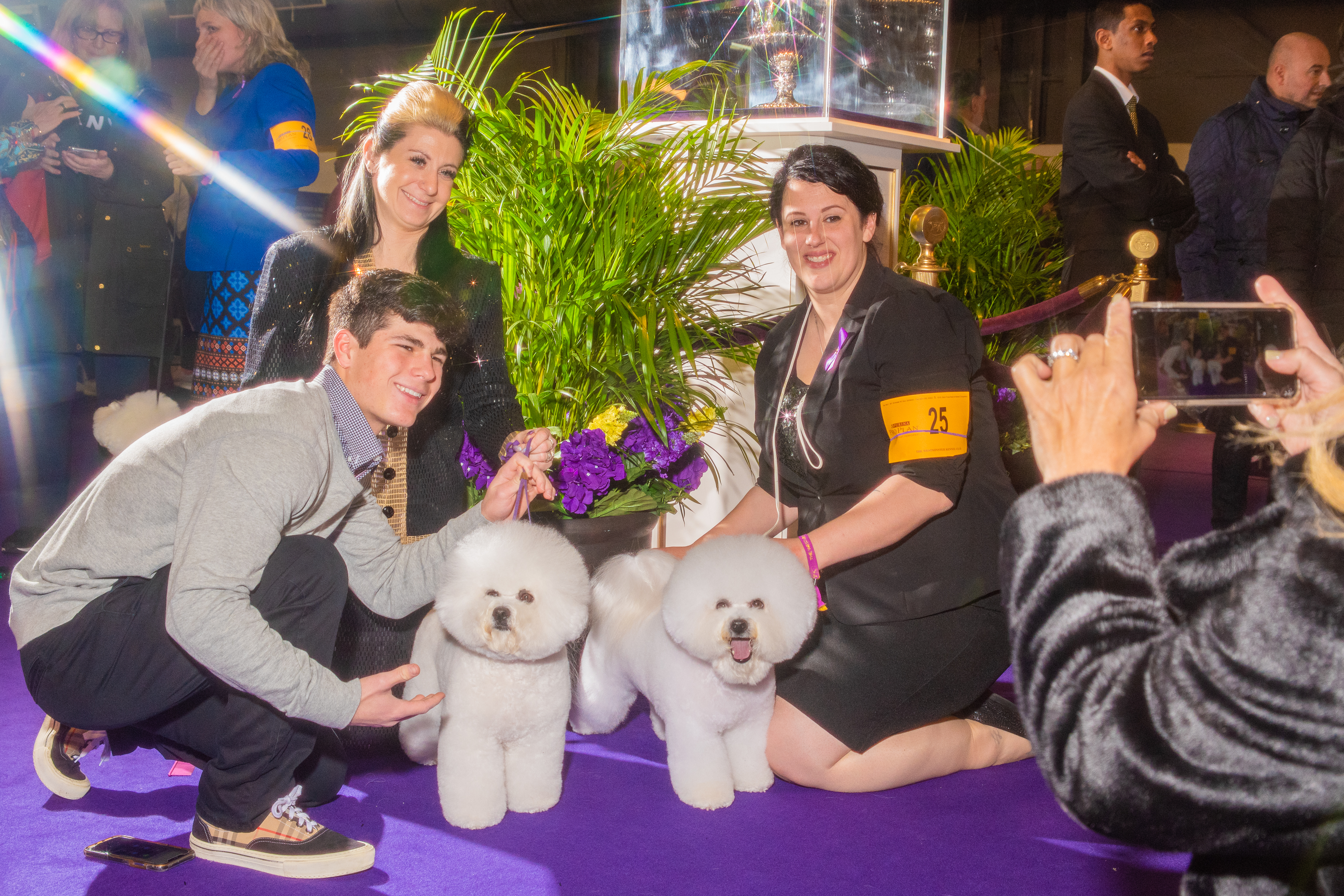 Attendees, photographed using a star filter, pose with two Bichons