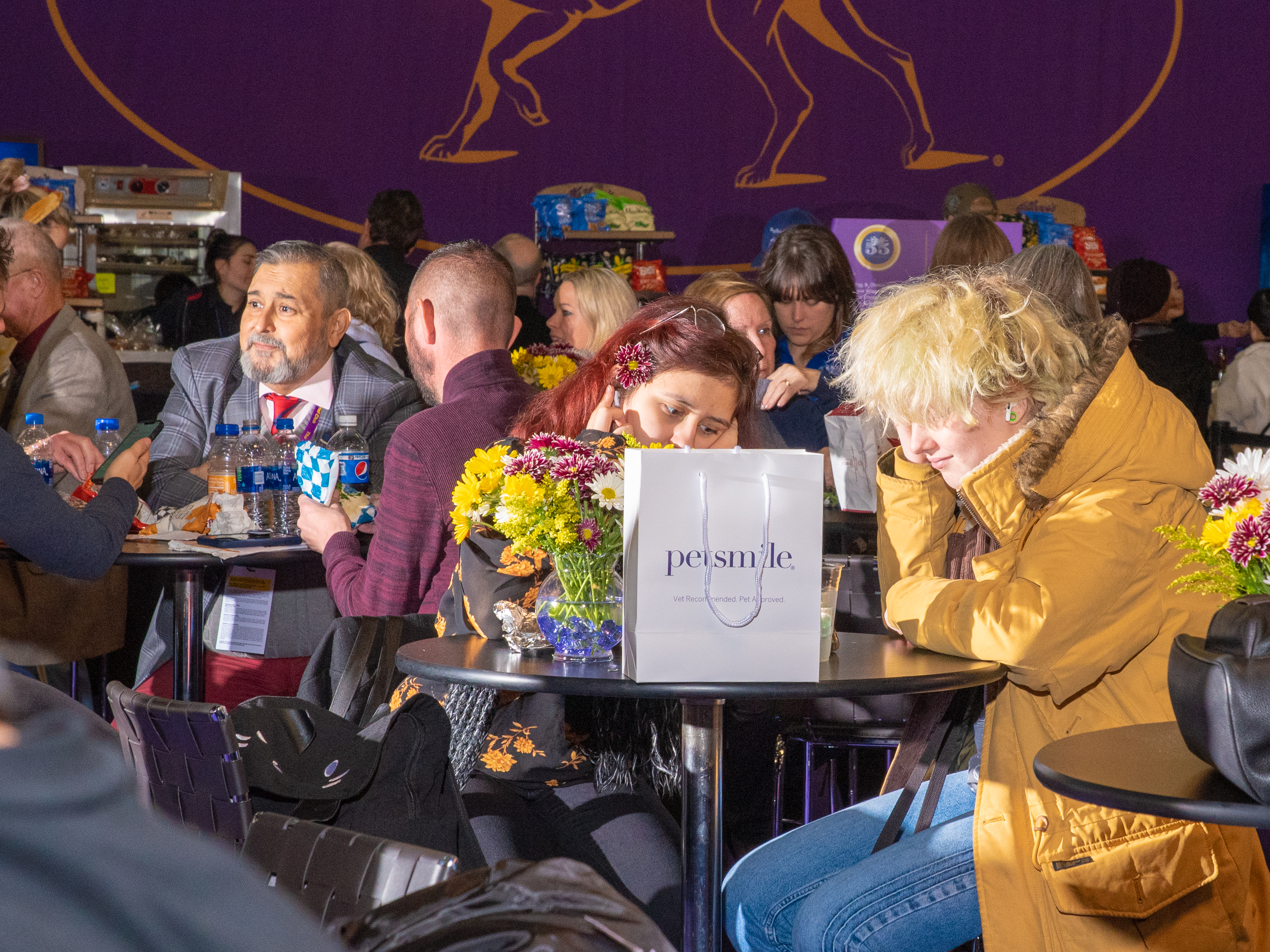 People hang out in the dining area at Pier 94 during the Westminster Dog Show