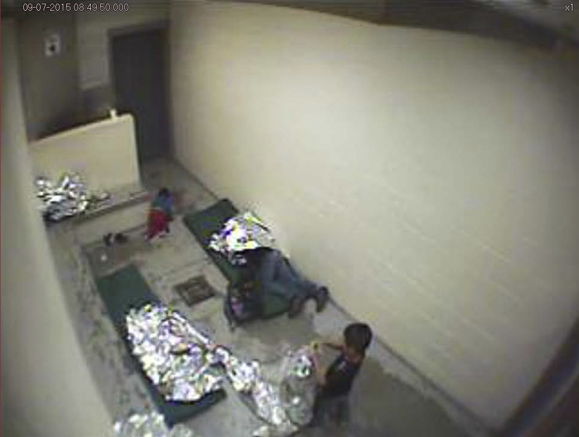 This image made from U.S. Border Patrol surveillance video shows a child crawling on the concrete floor near the bathroom area of a holding cell, and a woman and children wrapped in Mylar sheets at a U.S. Customs and Border Protection station in Douglas, Ariz., in September 2015.