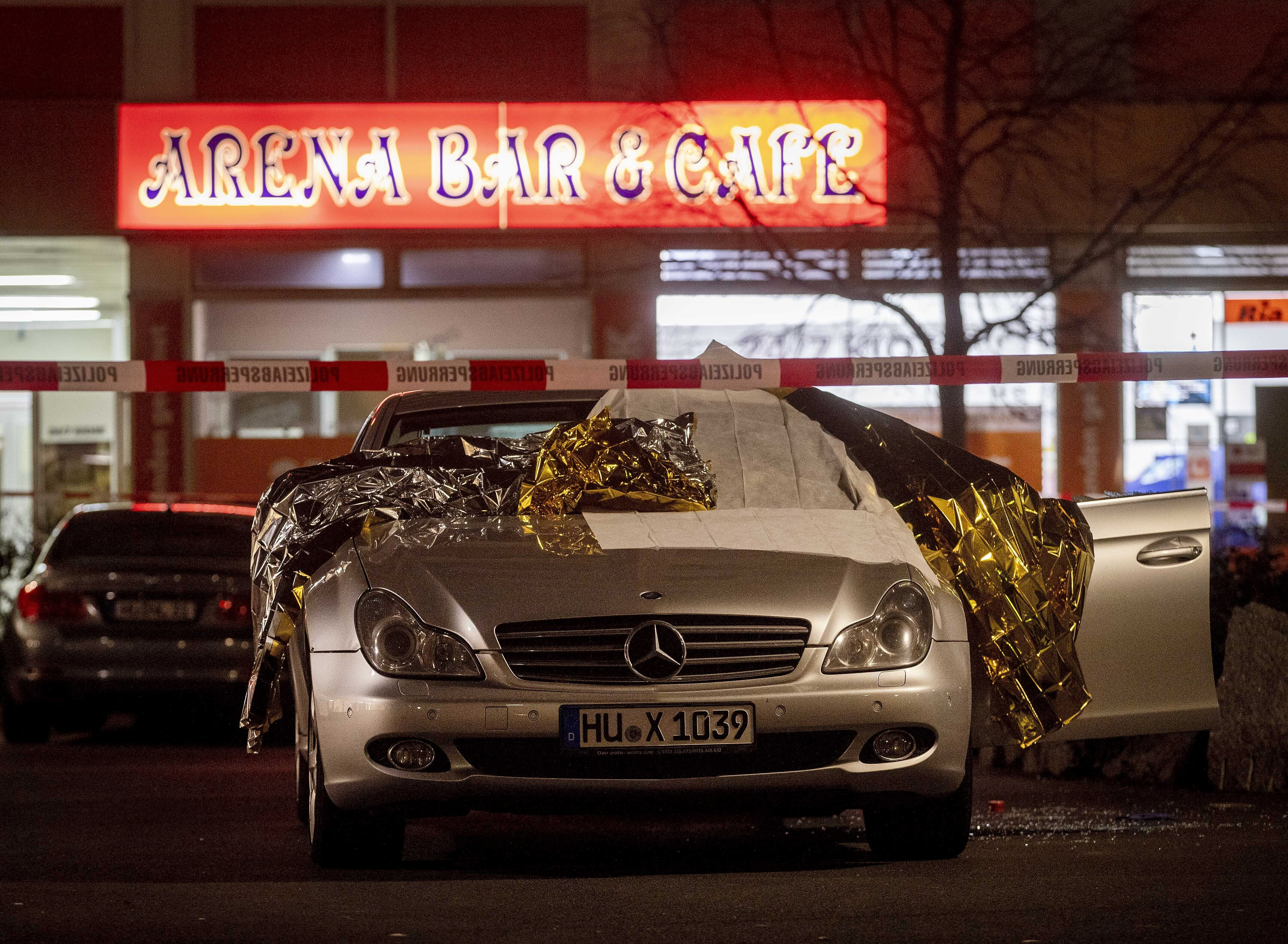 A car covered with rescue blankets stands in front of a bar in Hanau, Germany, on Feb. 20, 2020.
