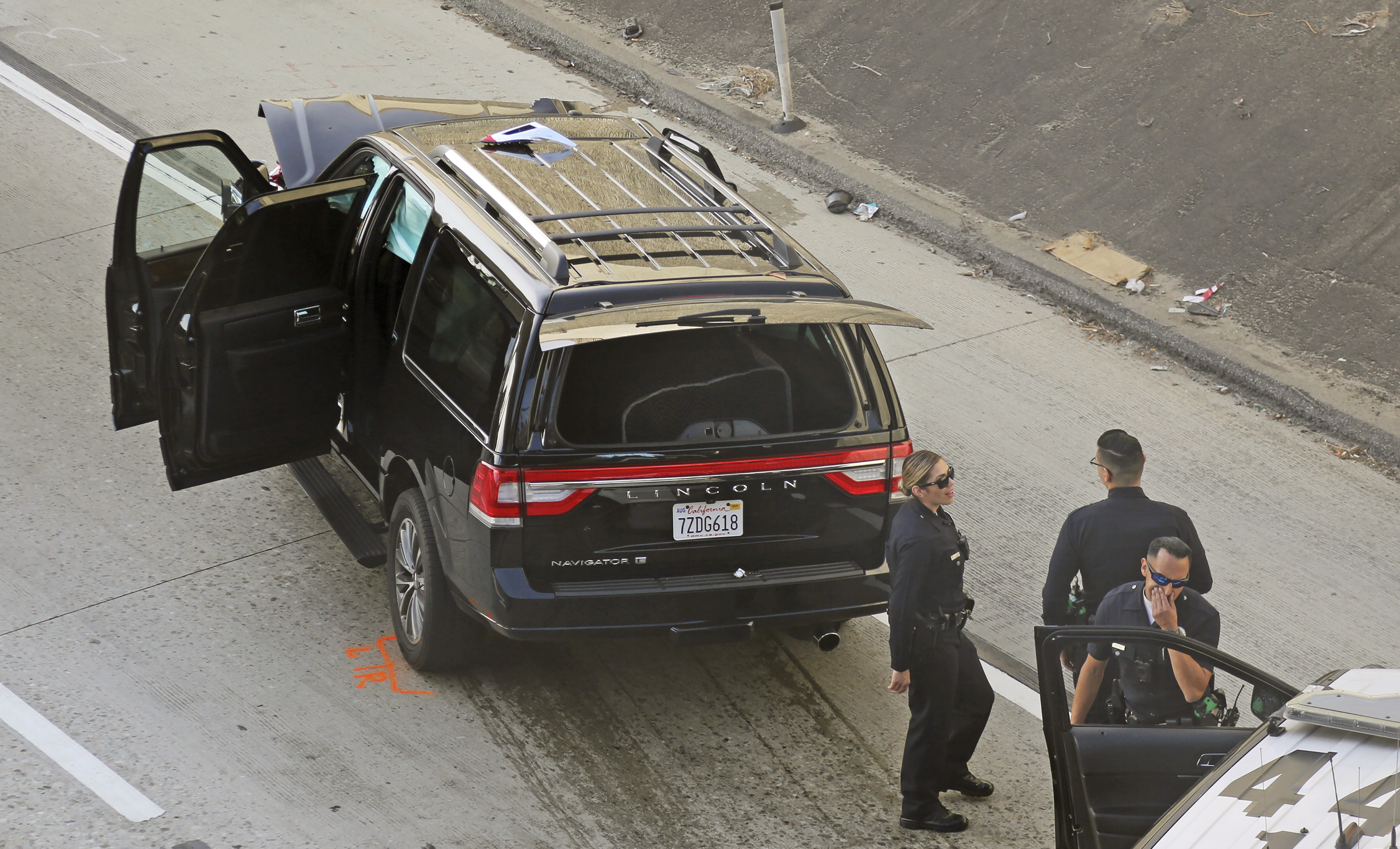 Los Angeles police officers stand after a pursuit of a stolen hearse with with a casket and body inside on Interstate 110 in South Los Angeles on Feb. 27, 2020.