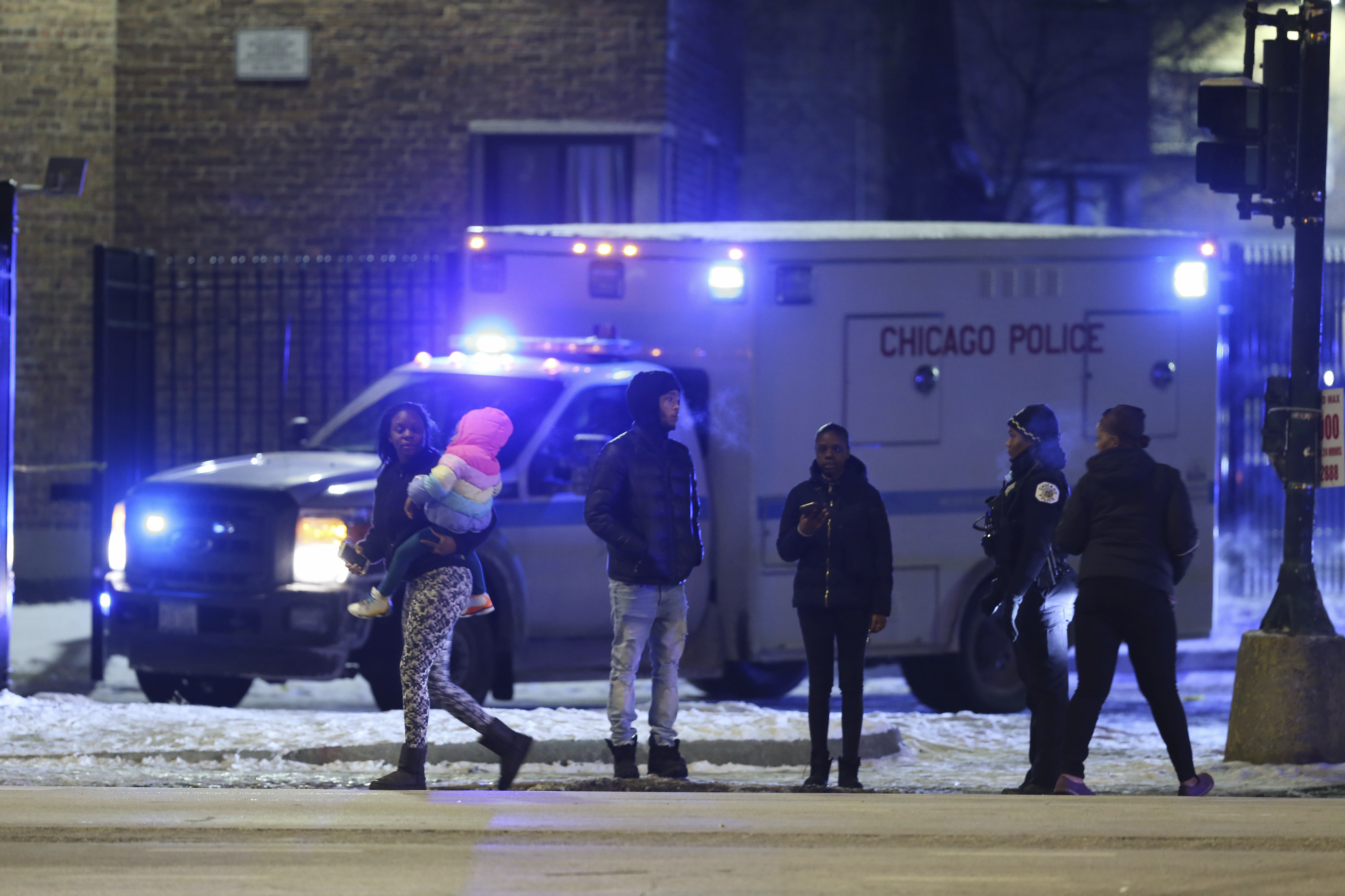 Emergency responders work the scene of a shooting on Feb. 14, 2020 in Chicago. Six people were wounded in the shooting at an apartment complex on Chicago's South Side, police said.