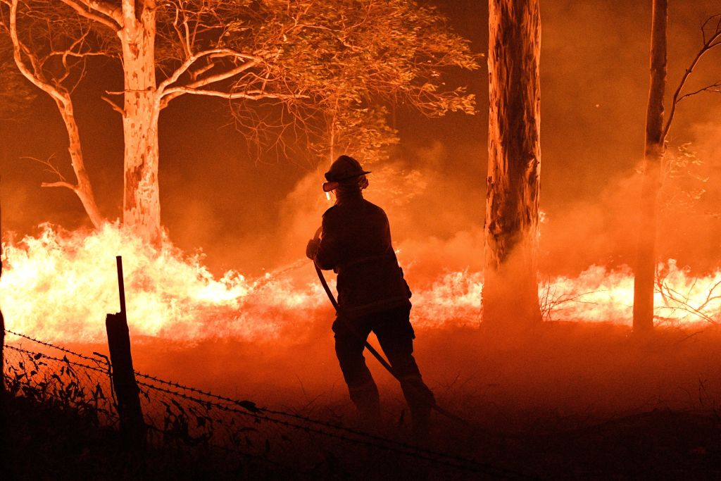 This picture taken on Dec. 31, 2019 shows a firefighter hosing down trees and flying embers in an effort to secure nearby houses from bushfires near the town of Nowra in the Australian state of New South Wales.