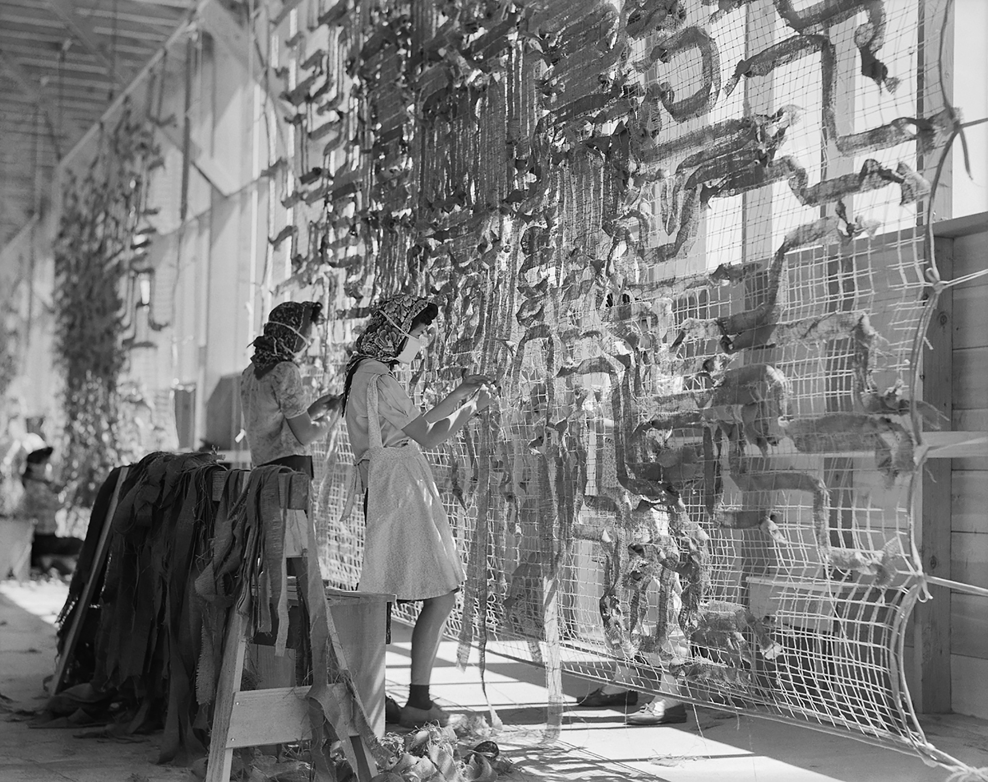 Manzanar Relocation Center, Manzanar, Calif. Making camouflage nets for the War Department. In 1942, Lange was commissioned to photograph the U.S. Government's imprisonment of Japanese Americans. Her negatives were impounded by the Army; she did not see them until 1964.