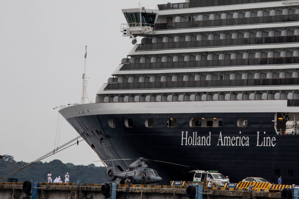 Health officials stand guard outside the MS Westerdam in Sihanoukville, Cambodia on Feb. 17, 2020. After the ship was declared free of coronavirus, one elderly American woman was later found to be infected while transiting in Malaysia.