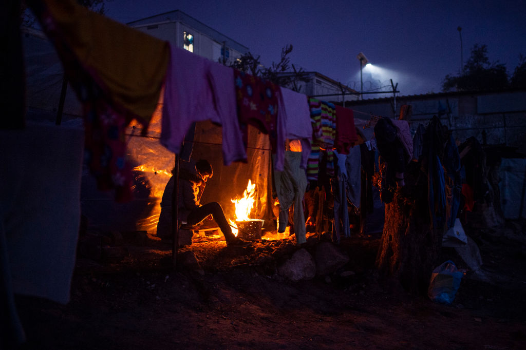 A migrant tries to warm himself in a temporary camp next to the camp in Moria by a small fire on January 22, 2020.