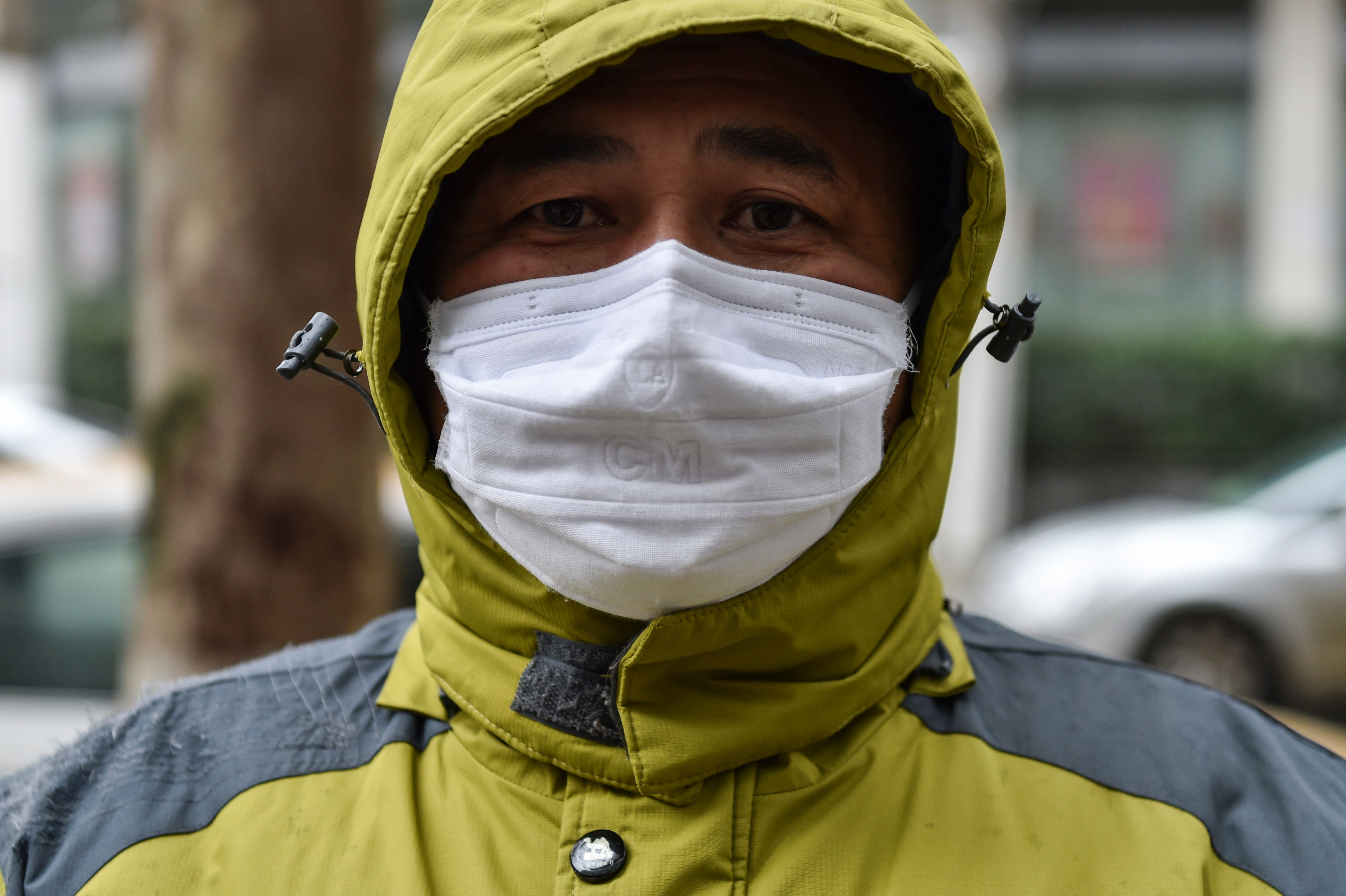 A man who works as a volunteer taking medicine for those who need it waits outside a pharmacy in Wuhan on January 26, 2020, the Chinese city at the epicenter of the coronavirus outbreak