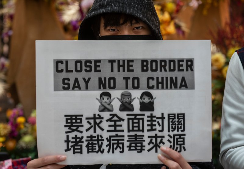 A Hong Kong demonstrator holds a placard during a protest calling on the government to close the border with China on Feb. 4, 2020.