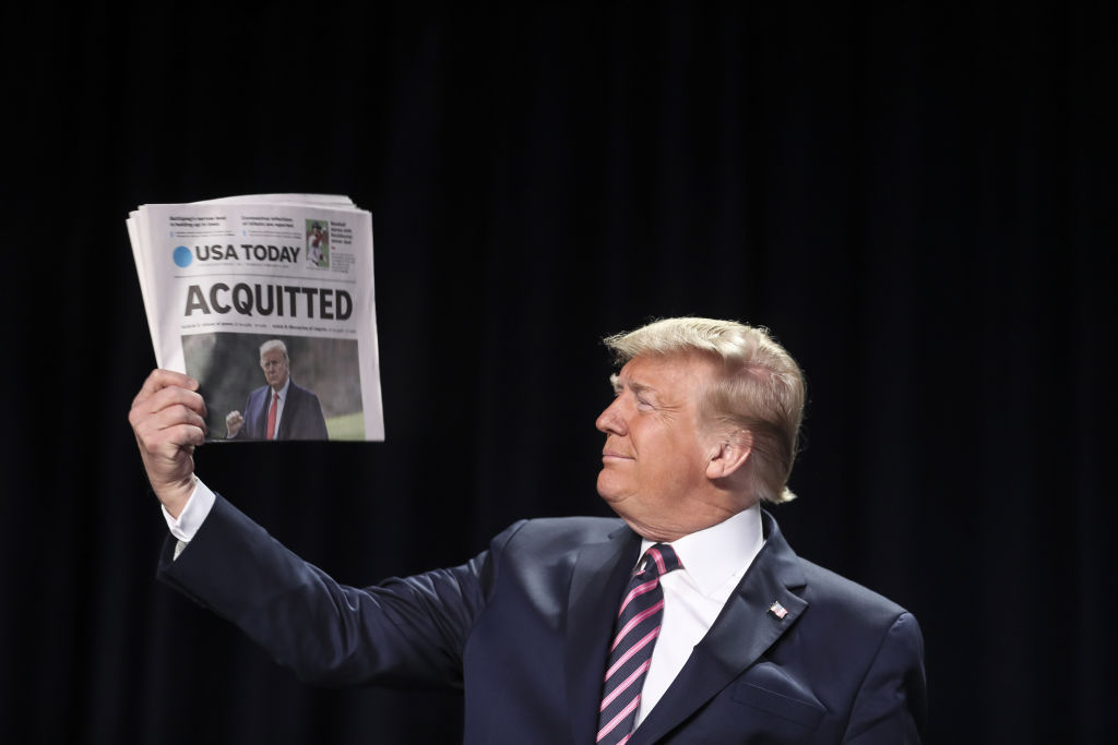 U.S. President Donald Trump holds up a copy of USA Today newspaper with a banner headline that reads  Acquitted  as he arrives to annual National Prayer Breakfast at the Washington Hilton in Washington, D.C., U.S., on Feb. 6, 2020.