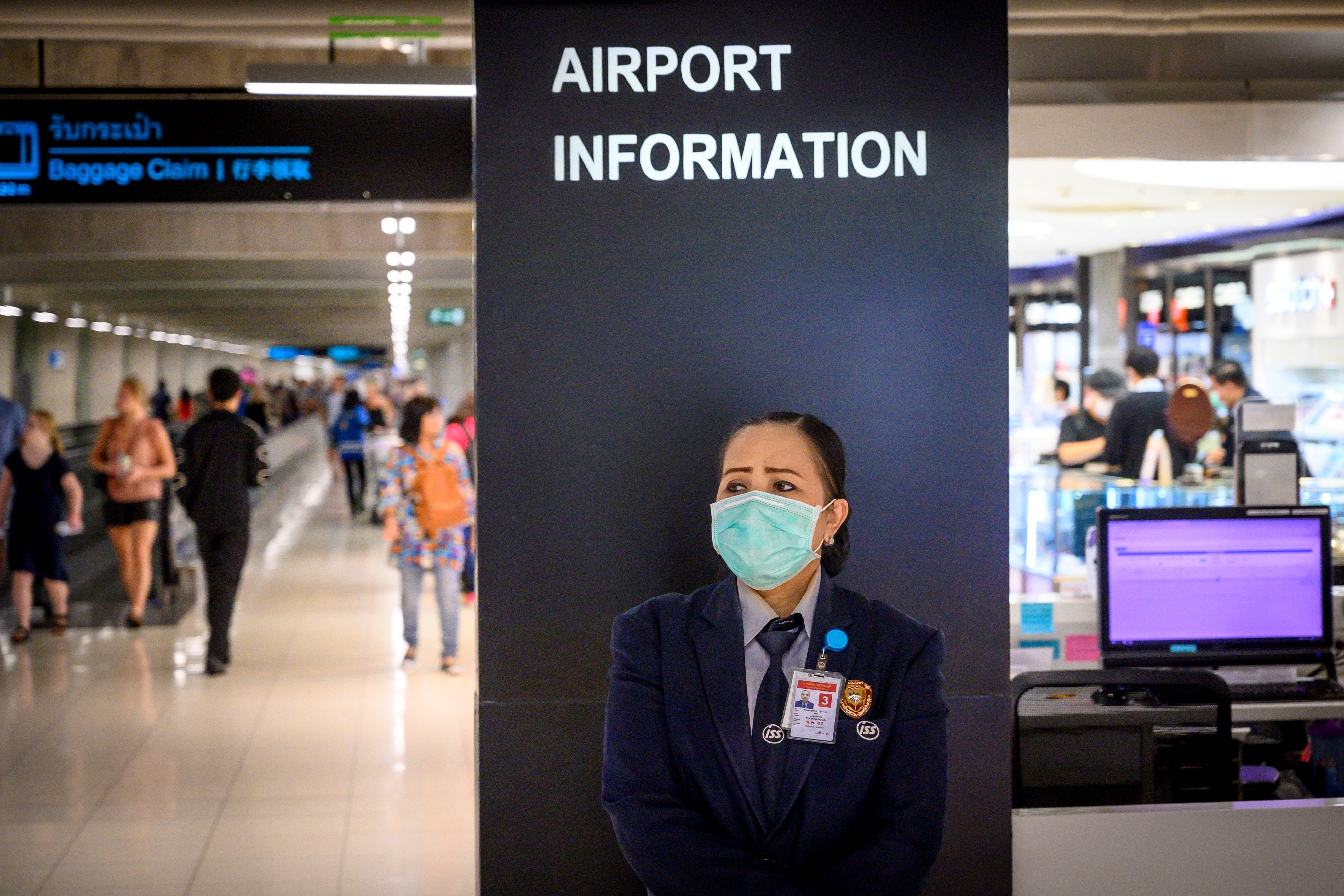 An airport staff member wearing a protective face mask stands at an information desk at Suvarnabhumi International Airport in Bangkok on Feb. 9, 2020.