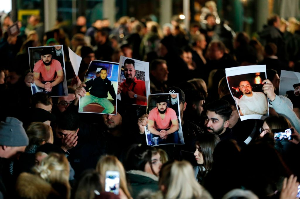 Mourners hold up photos, believed to be of victiims, during a vigil close to a crime scene in Hanau, near Frankfurt am Main, western Germany, on Feb. 20, 2020, after at least nine people were killed in two shootings late the night before.