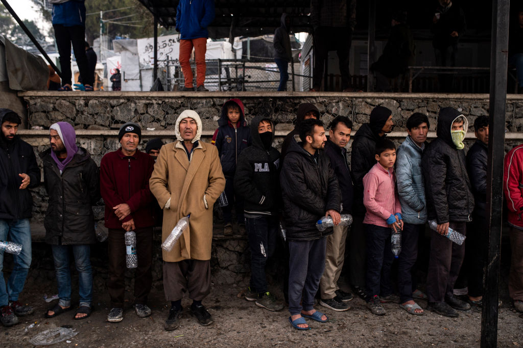 Migrants lined up await the distribution of food and water in the Moria refugee camp on February 2, 2020 in Moria, Greece.