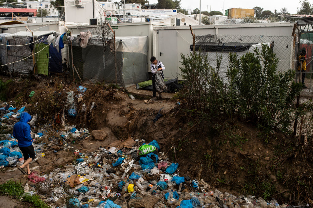 Migrants stand near an accumulation of garbage in the stream of the Moria refugee camp on February 5, 2020 in Moria, Greece.