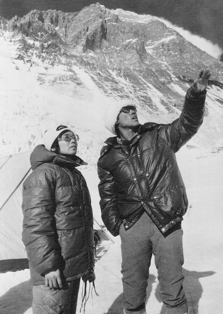 Junko Tabei (L), then 35, the first woman ever to conquer the world's highest peak, stands against the background of the southern wall of Mt. Everest.