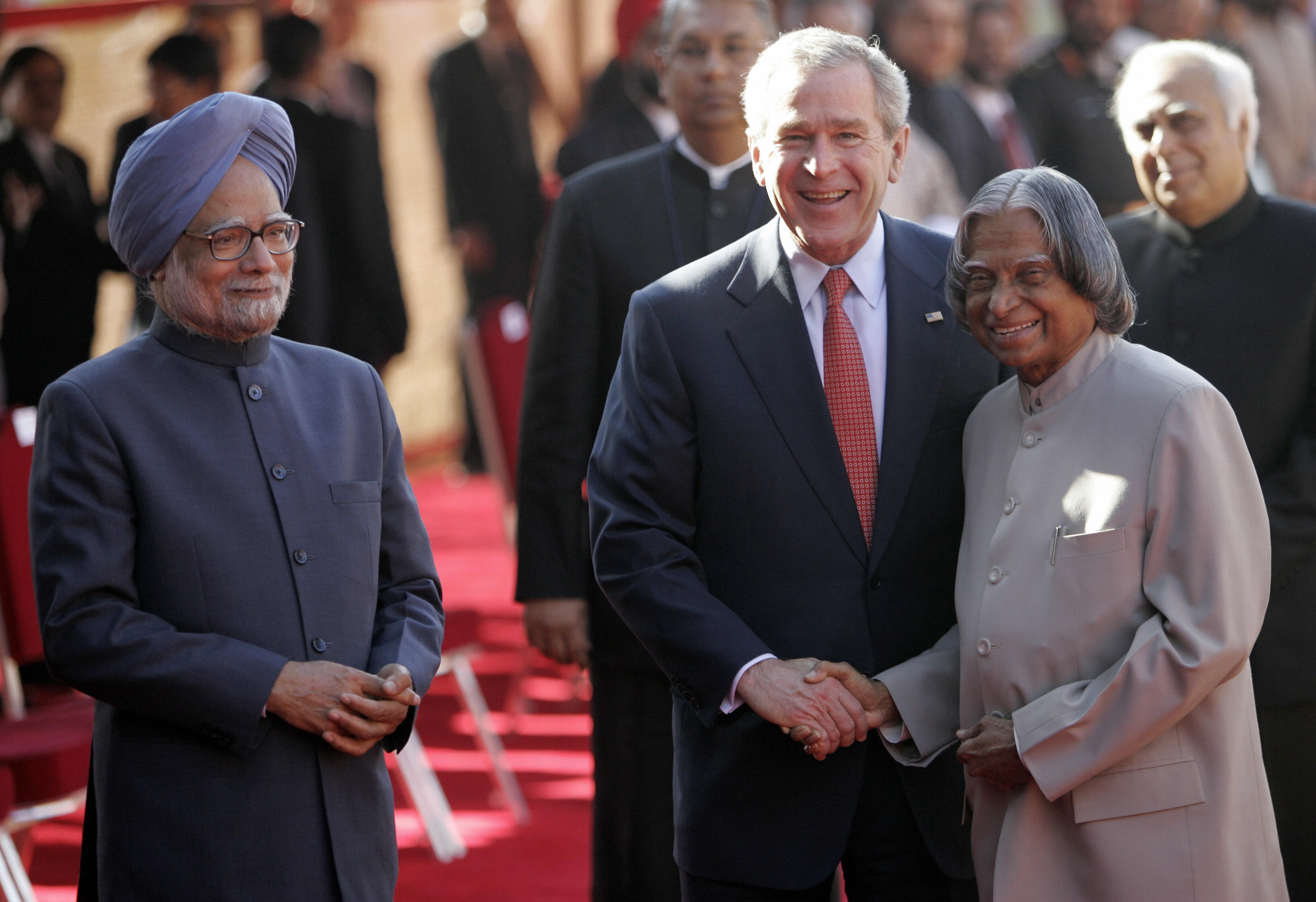 U.S. President George W. Bush shakes hands with Indian President A.P.J. Abdul Kalam while Prime Minister Manmohan Singh looks on during an official welcoming ceremony at the Presidential Palace in New Delhi on March 2, 2006.