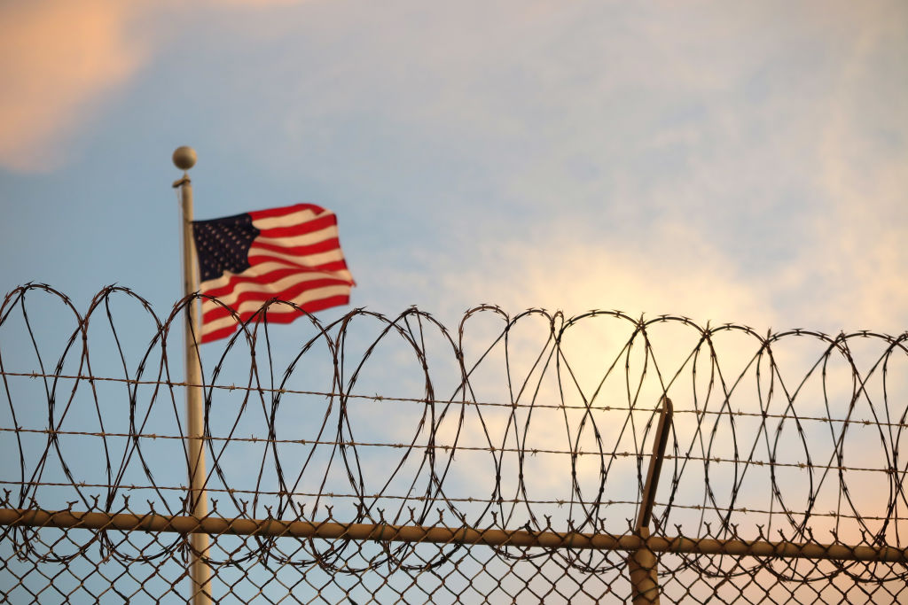 The American flag blows behind a barbed wire fence in the wind in Guantanamo Bay, Cuba on Oct. 16, 2018.